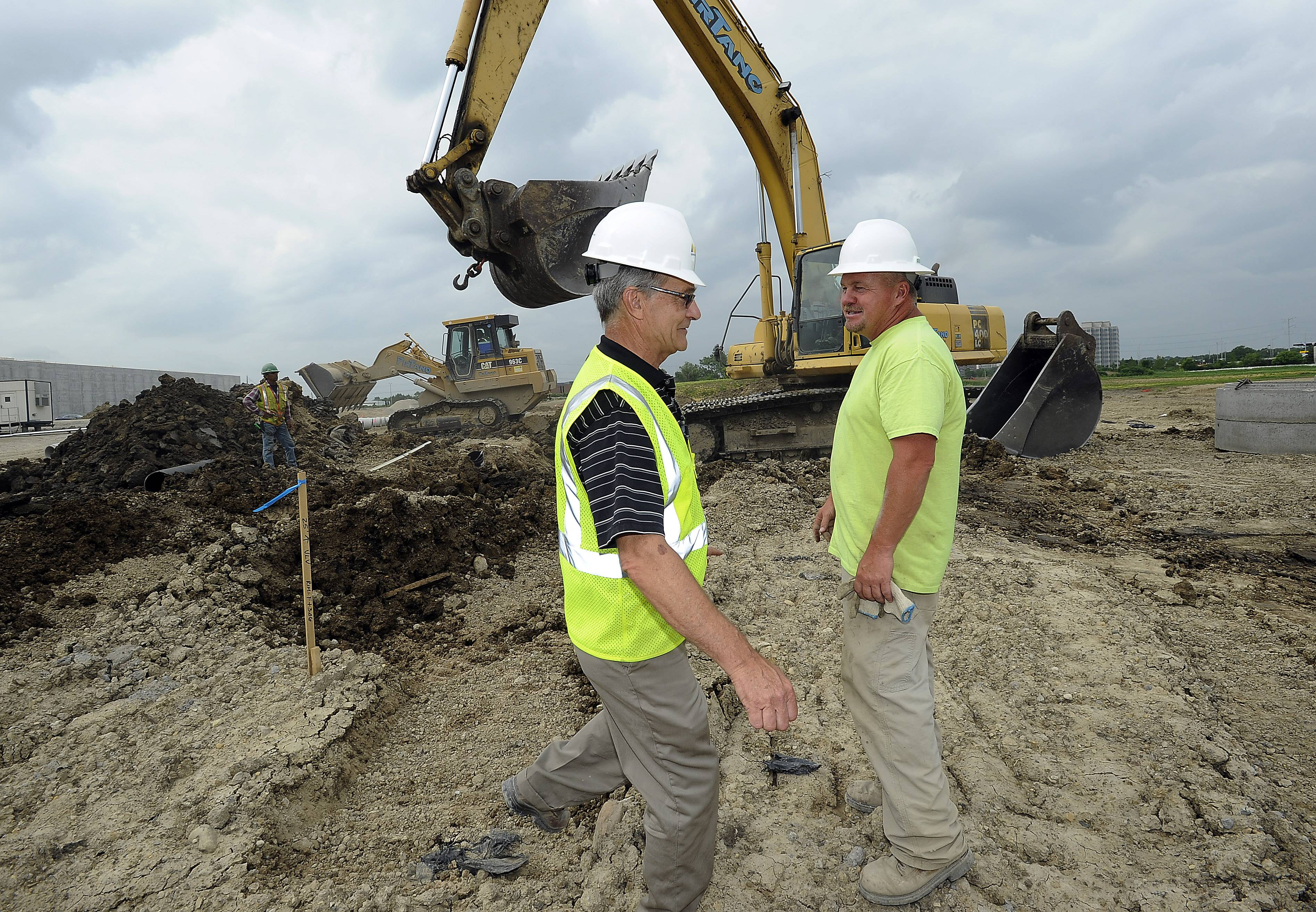 Bill Nielsen of Peak Construction Corp., left, talks with Chuck Young, sewer foreman, at the Sunstar Americas Inc. job site. The company's new national headquarters is will open in 2015.