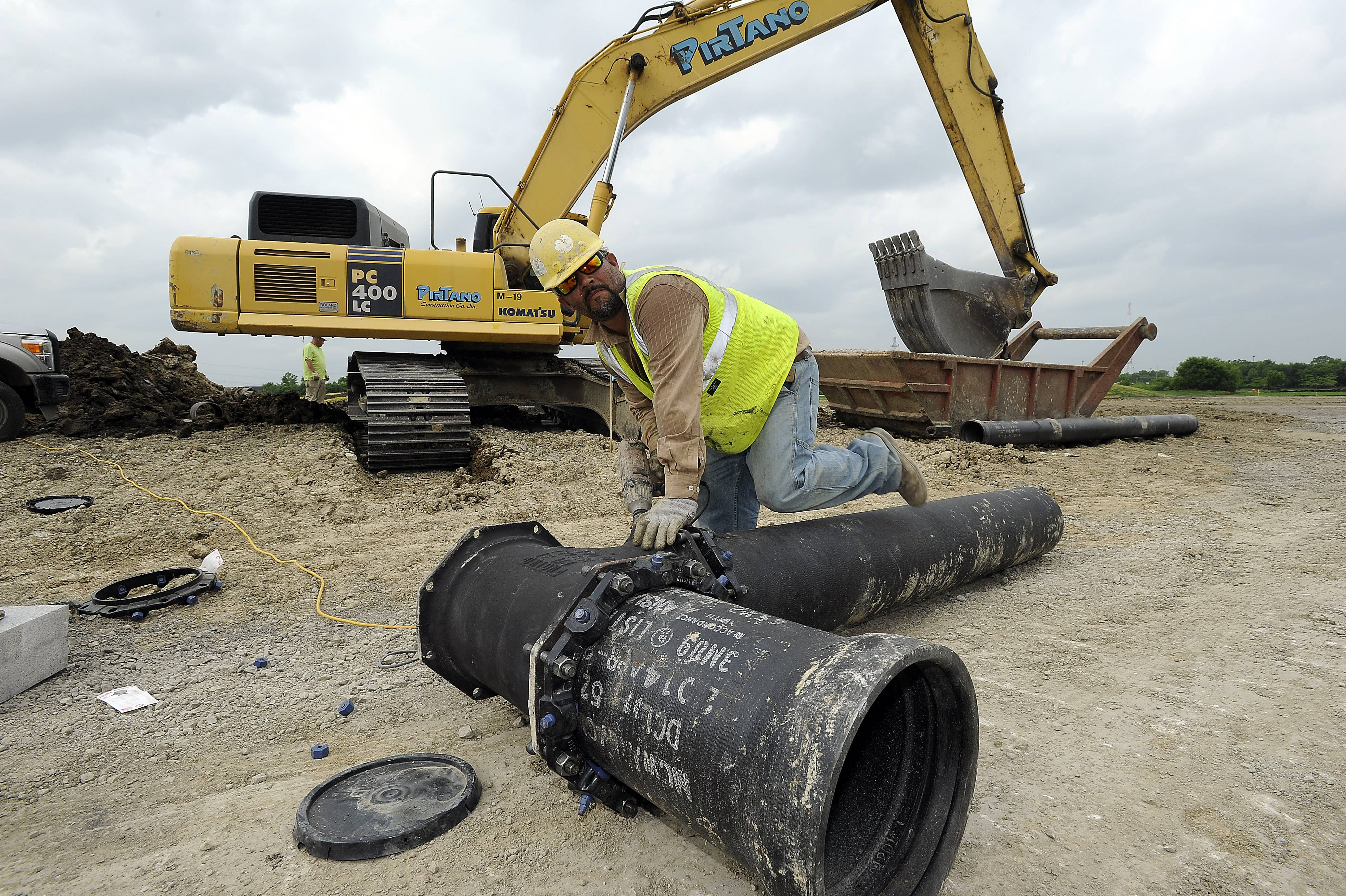 Ray Solis of Peak Construction Corp. puts in a water line at the new national headquarters of Sunstar Americas Inc.