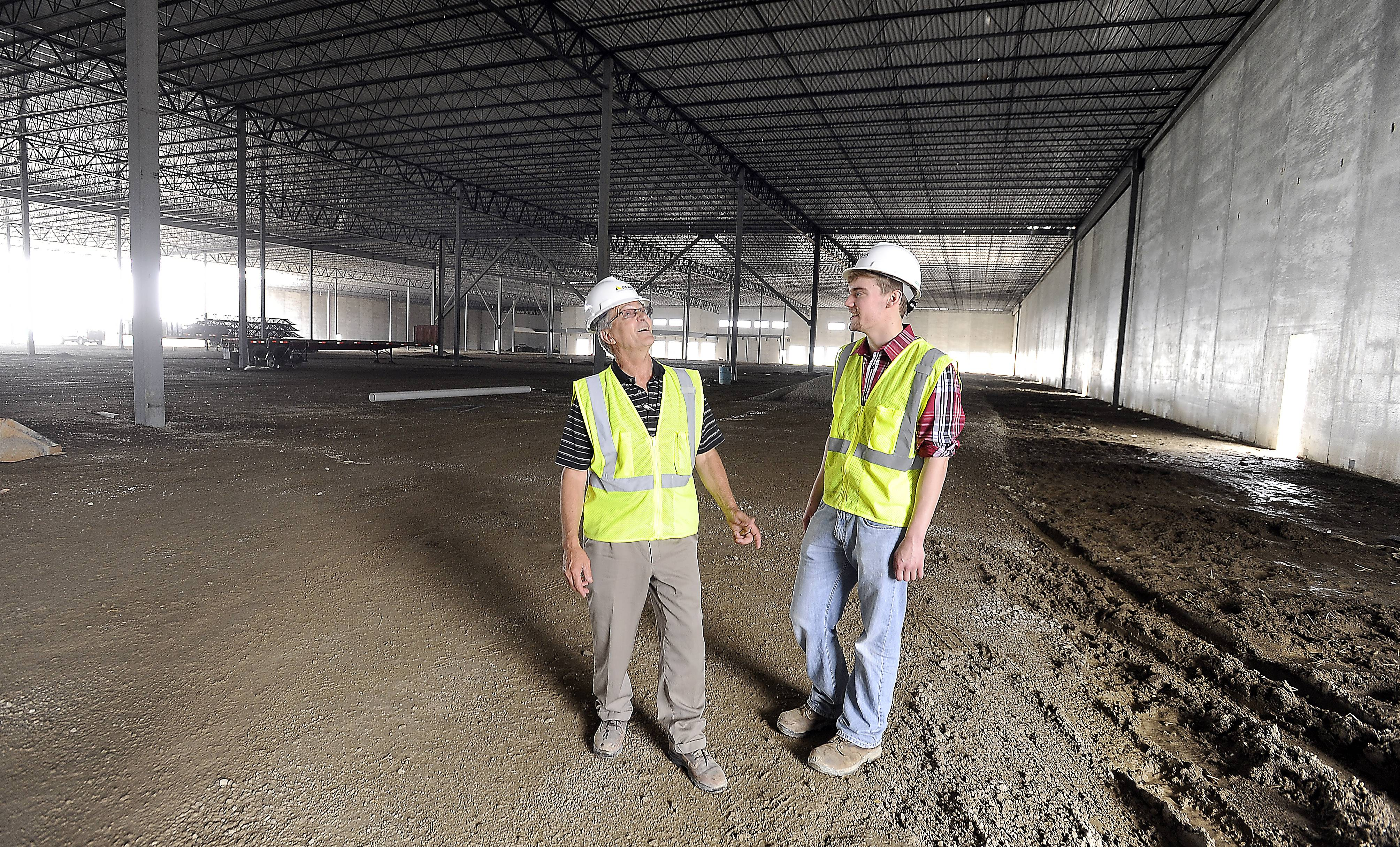 Bill Nielsen of Peak Construction Corp., left, talks with Marc Alexander, project engineer intern, at the job site of Sunstar Americas Inc.