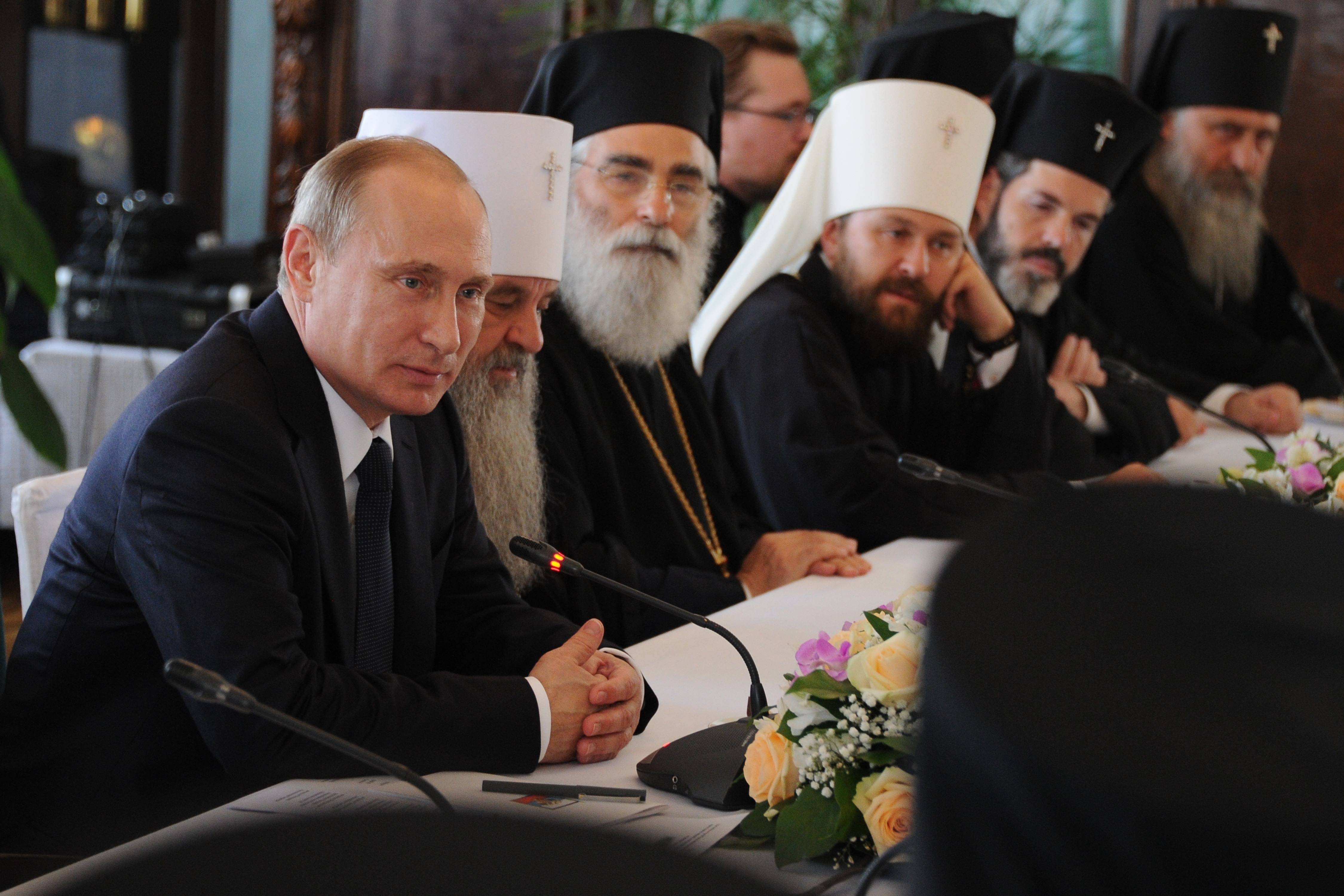 Russian President Vladimir Putin, left, attends celebrations marking the 700th anniversary of St. Sergius of Radonezh in the Trinity St. Sergius monastery in Sergiyev Posad, northeast of Moscow.