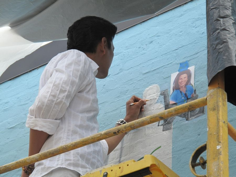 "Lead artist Dodie Mondero of Orland Park outlines the image of NCTV Executive Director Liz Spencer as part of the ""Naperville Loves a Parade"" mural in downtown Naperville. Work on the mural began four years ago and the piece is scheduled to be dedicated after this year's Labor Day parade."