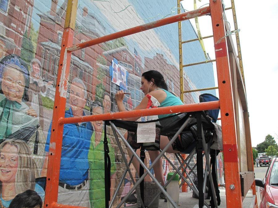 "The ""Naperville Loves a Parade"" mural is nearing completion and scheduled for a Labor Day dedication. Here, artist Adela Vystejnova paints the Judd Kendall VFW Post 3873 into the scene."