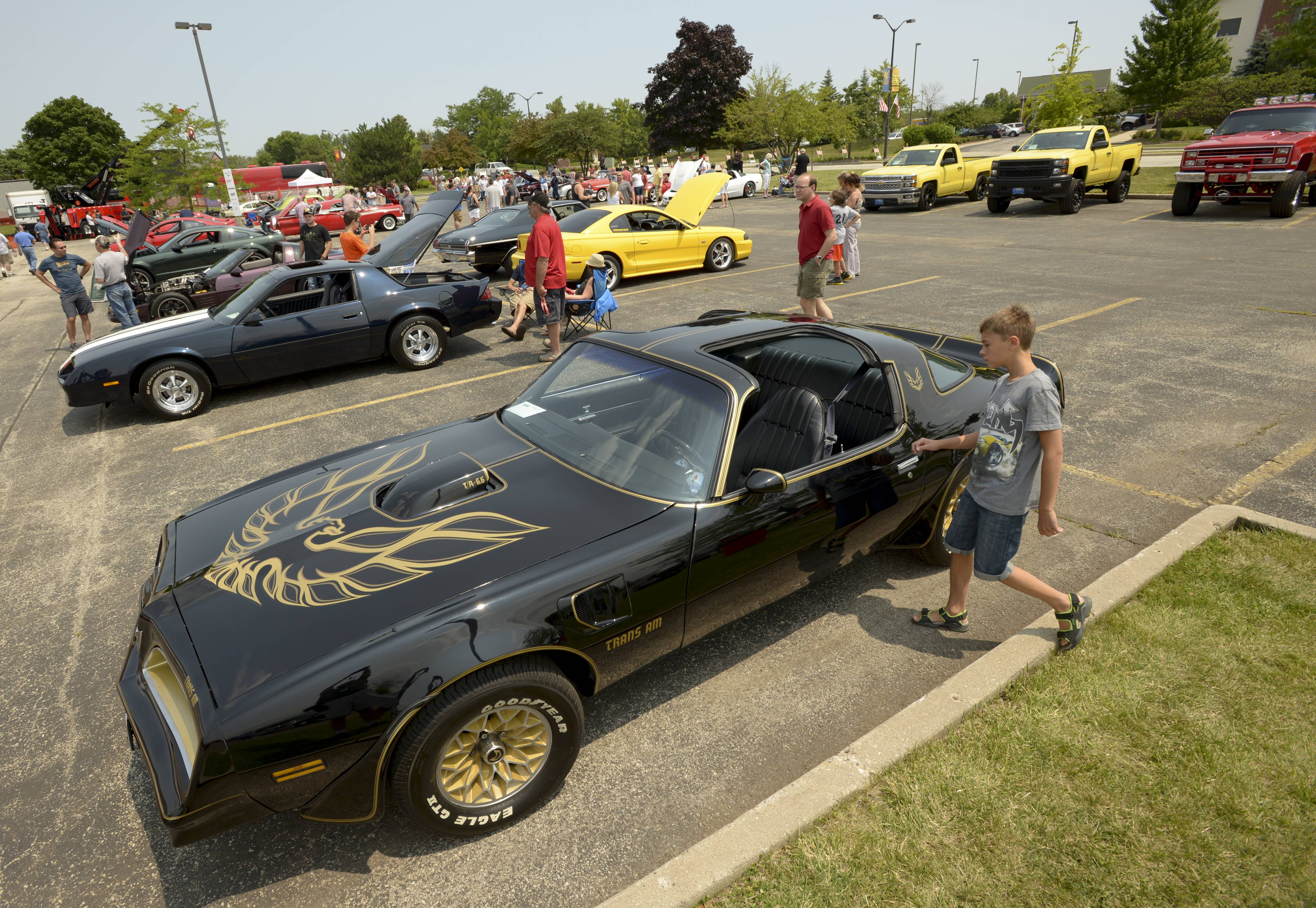 Car buffs check out the vehicles at the inaugural car show during the Vernon Hills Summer Celebration Saturday.