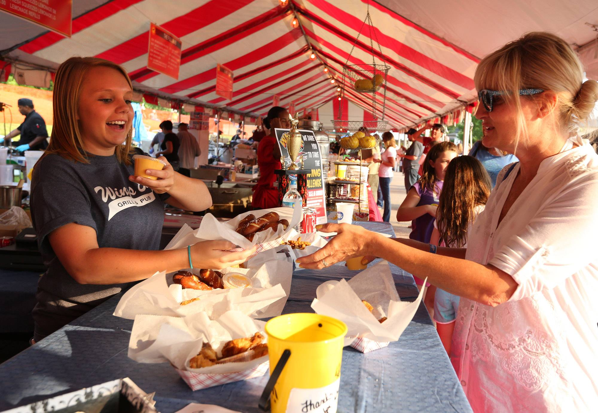Daryl Gussarson, of Antioch, working the Wings Etc. of Antioch booth, serves pretzels to Laura Sokniewicz of Chicago, at the second day of the Antioch Taste of Summer on Friday.