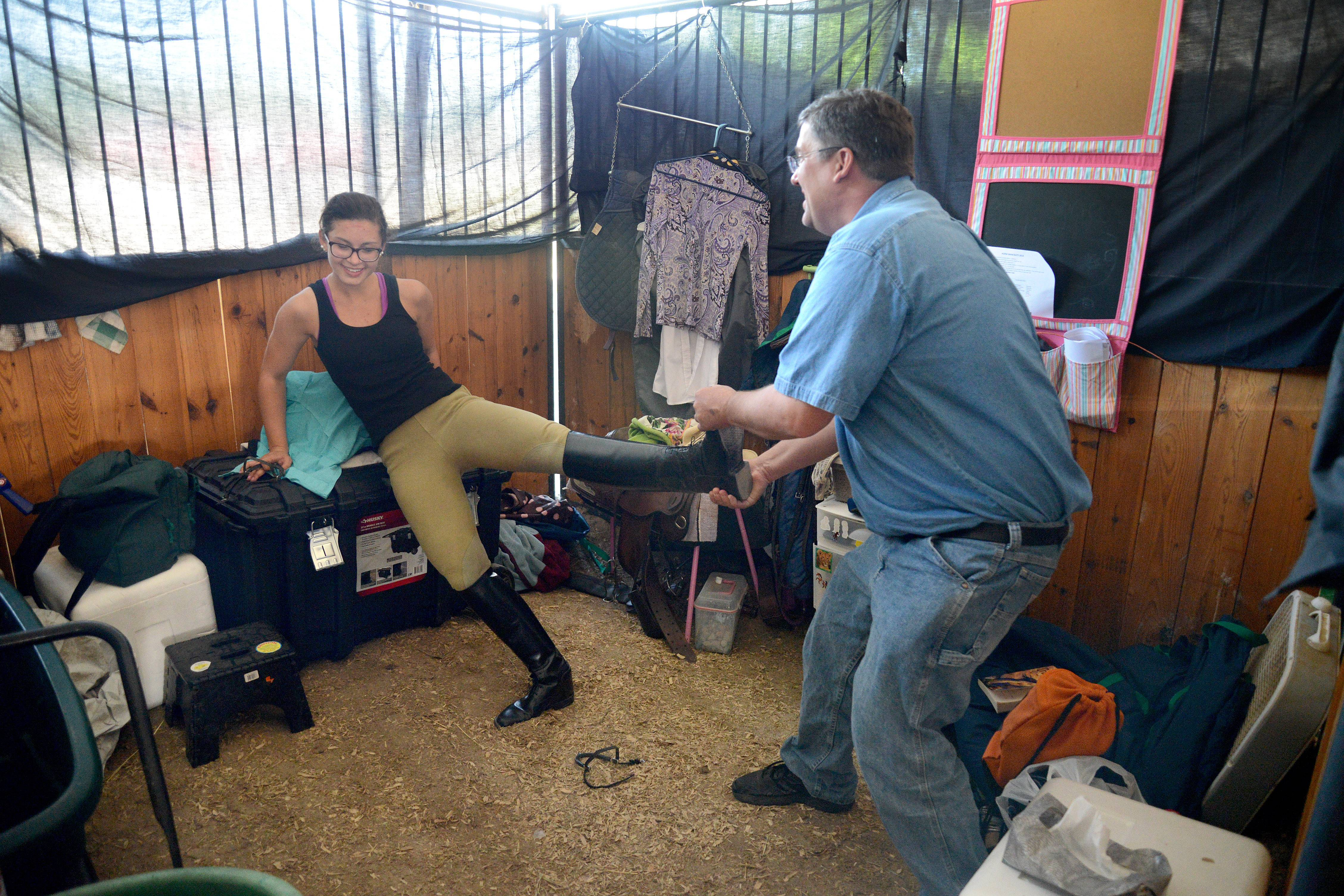 Madde Klinkey, 15, of Wasco gets help from her father, Rob, with getting her boots off after competing at the Kane County Fair.
