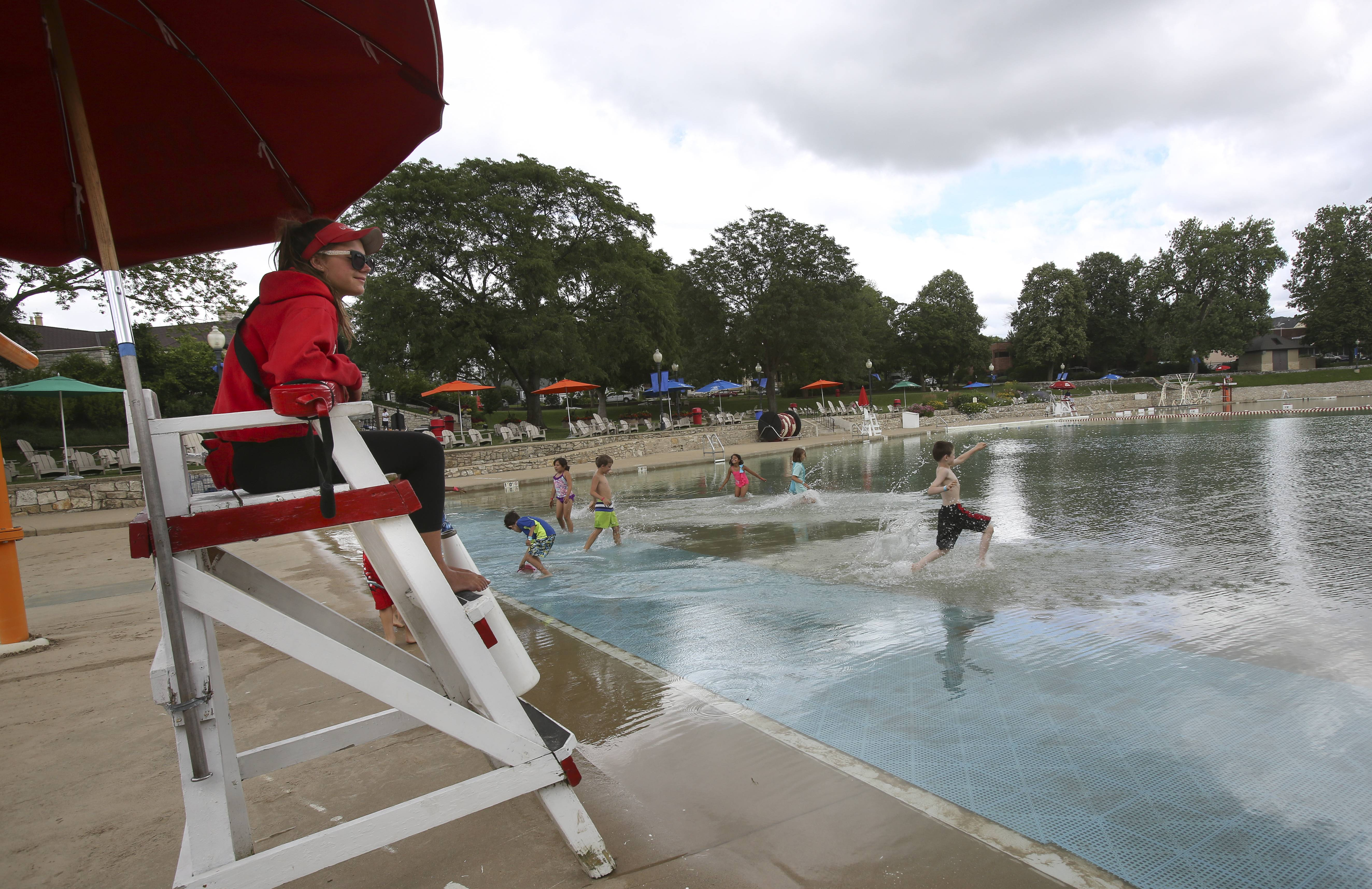 Lifeguard Sarah Pilgrim keeps an eye on the few kids braving the cold waters at Centennial Beach in Naperville on Tuesday. The water did not open to swimmers until 11:40 am, when the temperature reached 65 degrees.
