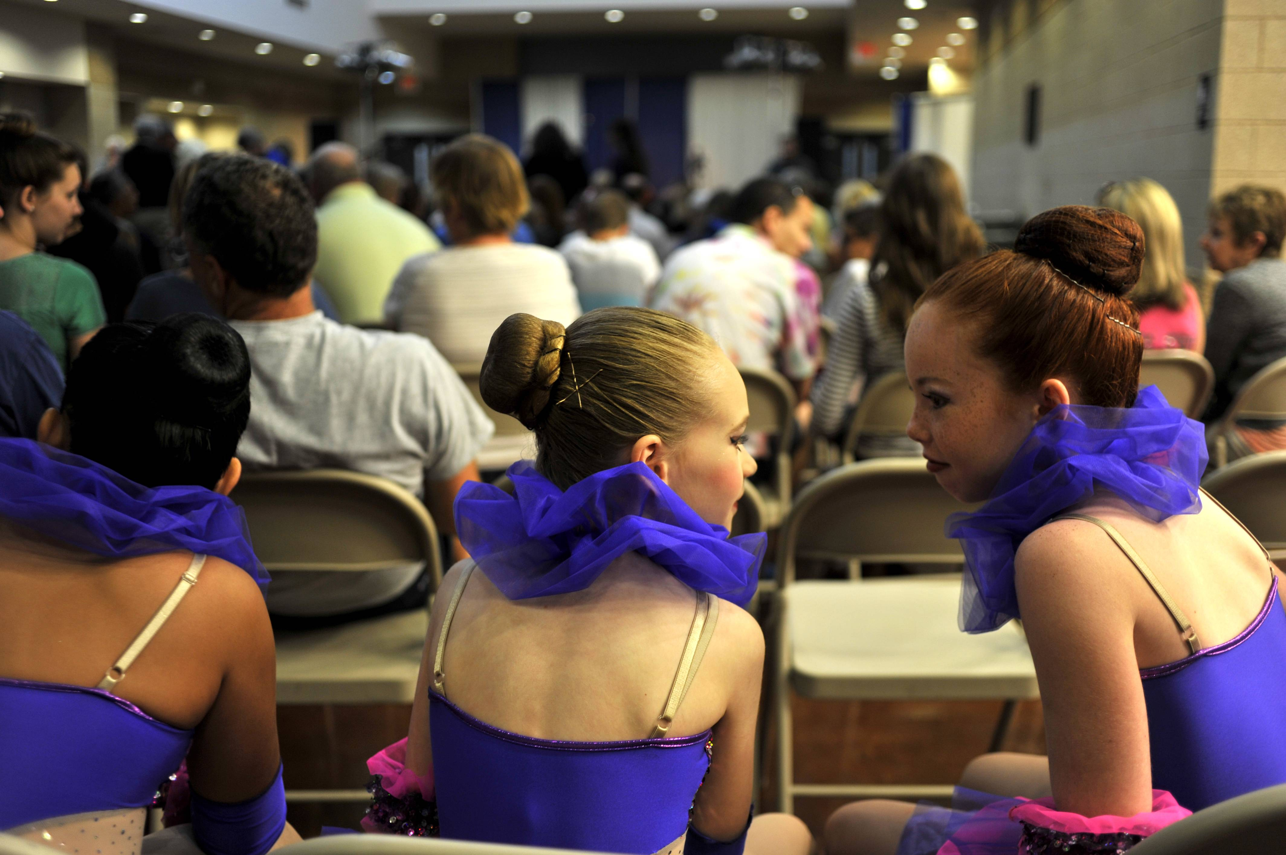 Mia Soderquist Hansen, 10, of St. Charles, center, and CJ Silverman, 9, of Geneva, share secrets before they and the other members of the Geneva Cosmic Girls dance at the Kane County Talent Show at Kane County Fairgrounds in St. Charles on Monday. The girls are all from St. Charles and Geneva and danced jazz at the competition.