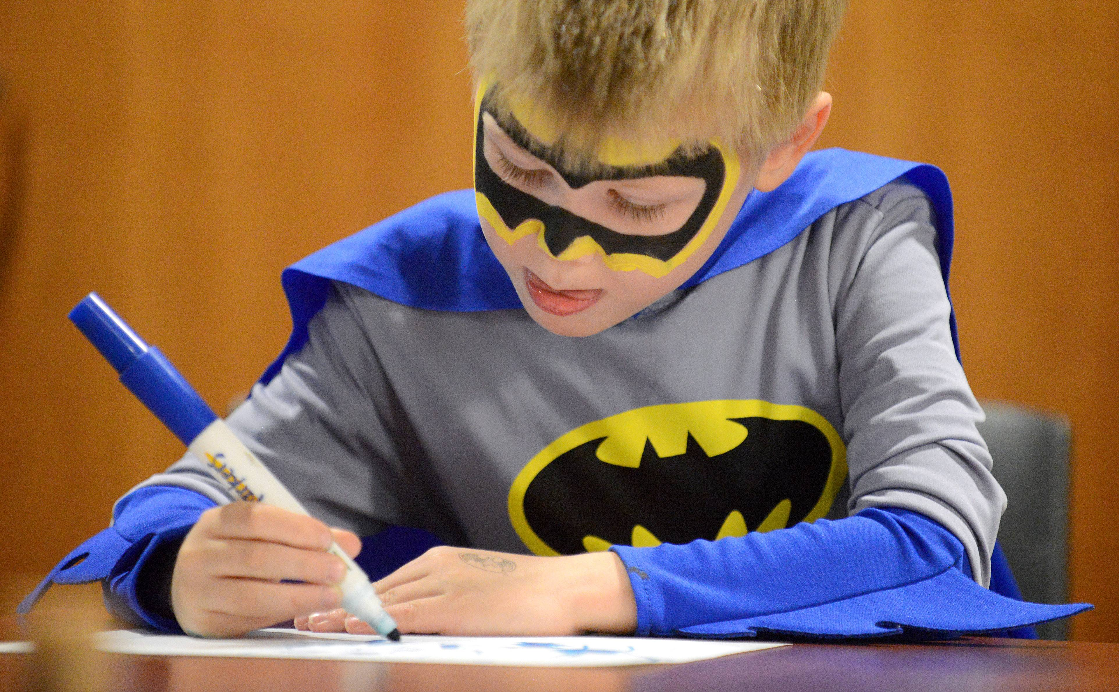 "Caleb Reinheimer, 6, of Elgin, draws his own three-panel comic book sketch at the fifth annual Comic Book Mania Convention at the Gail Borden Library in Elgin on Saturday. Caleb's favorite comic book characters are Bataman and the Teenage Ninja Turtles, ""Because Batman needed friends,"" says Caleb."