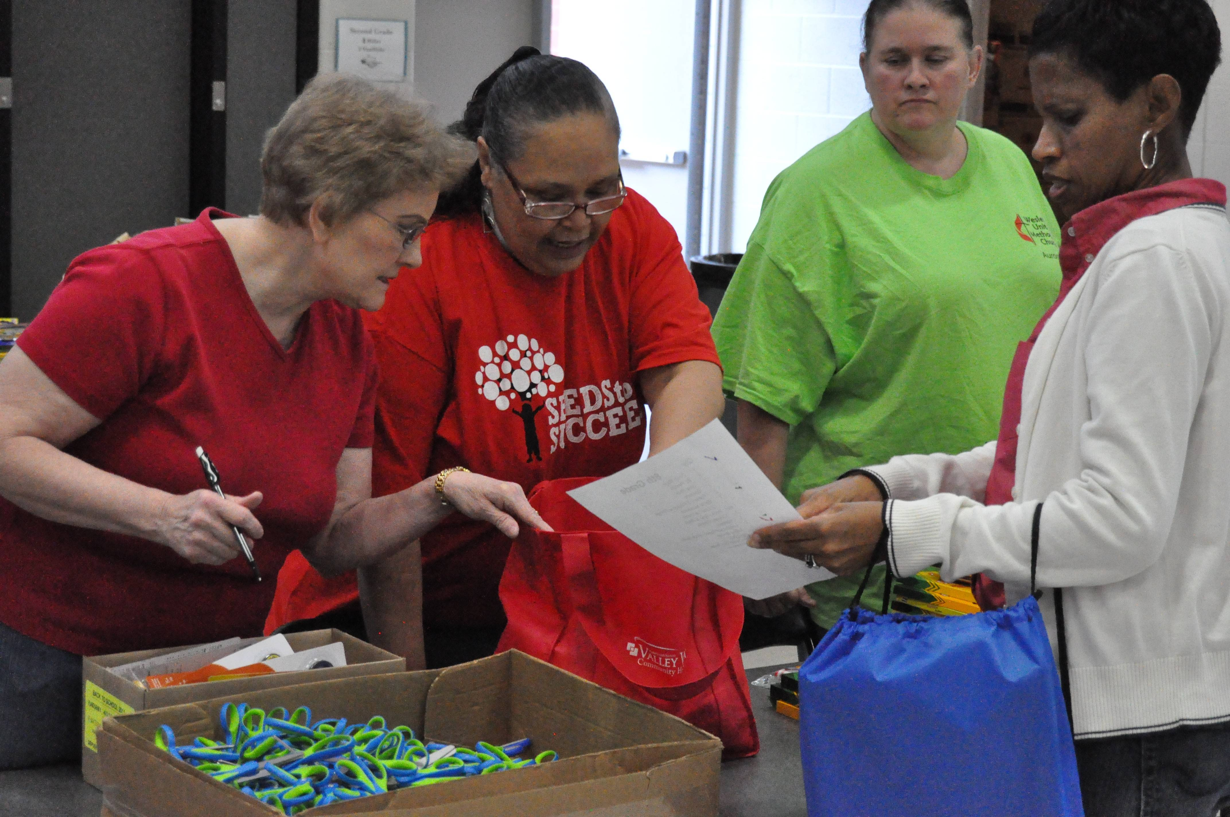 Karen Whipple, left, and the Rev. Deborah Tinsley Taylor, center, pastor at Fourth Street United Methodist Church in Aurora, were among the volunteers last year distributing donated school supplies at Greenman Elementary School in Aurora. This year's giveaway will be Saturday, Aug. 9.