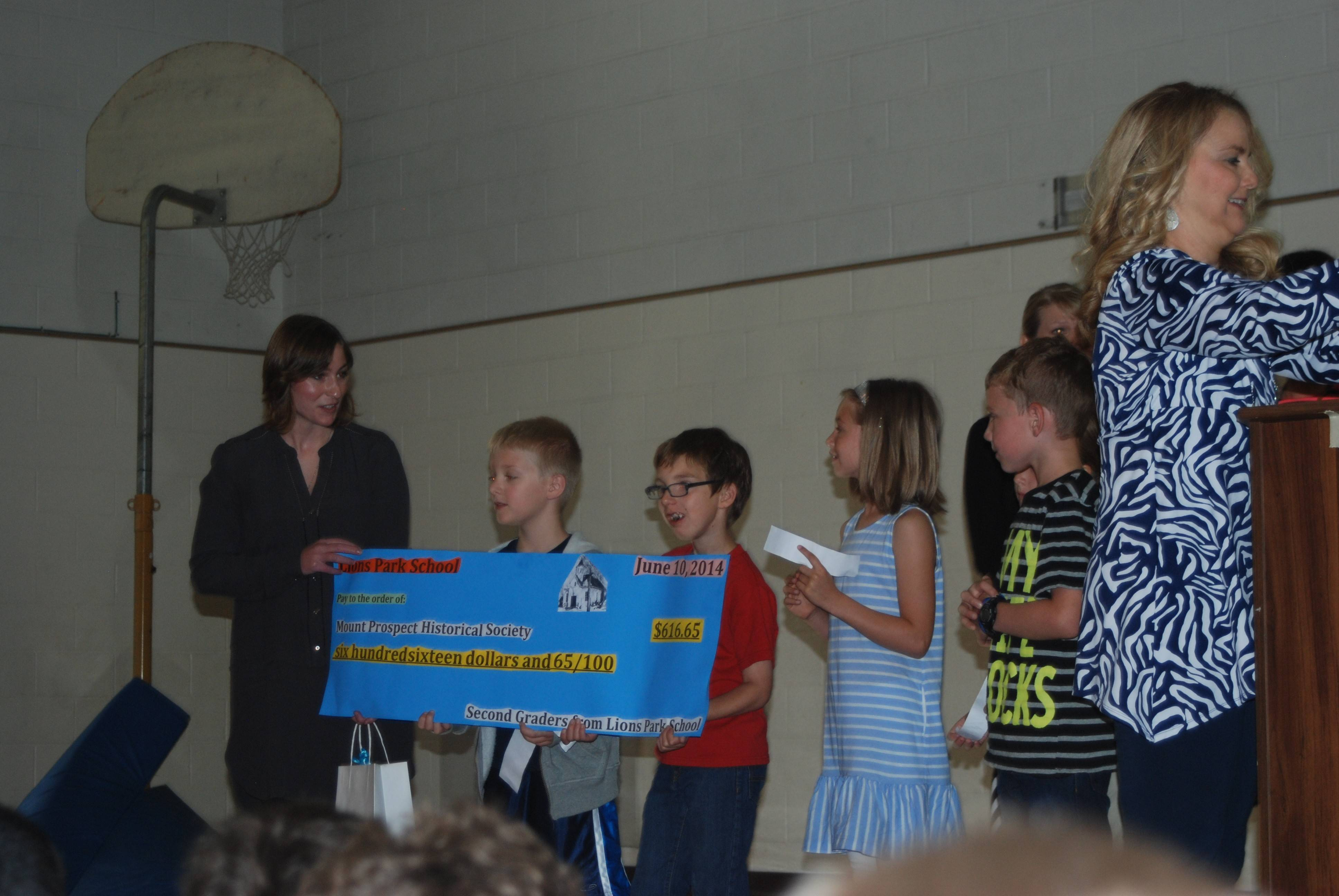 Mount Prospect Historical Society's executive director Lindsay Rice, left, is presented with a check from the second-grade students at Lions Park School. Students, from left, are: Roman Demstrom, Thomas Haban, Charlotte Deines, and Nolan Hahn. Mary Hunt is the teacher in front retrieving the microphone for the students.
