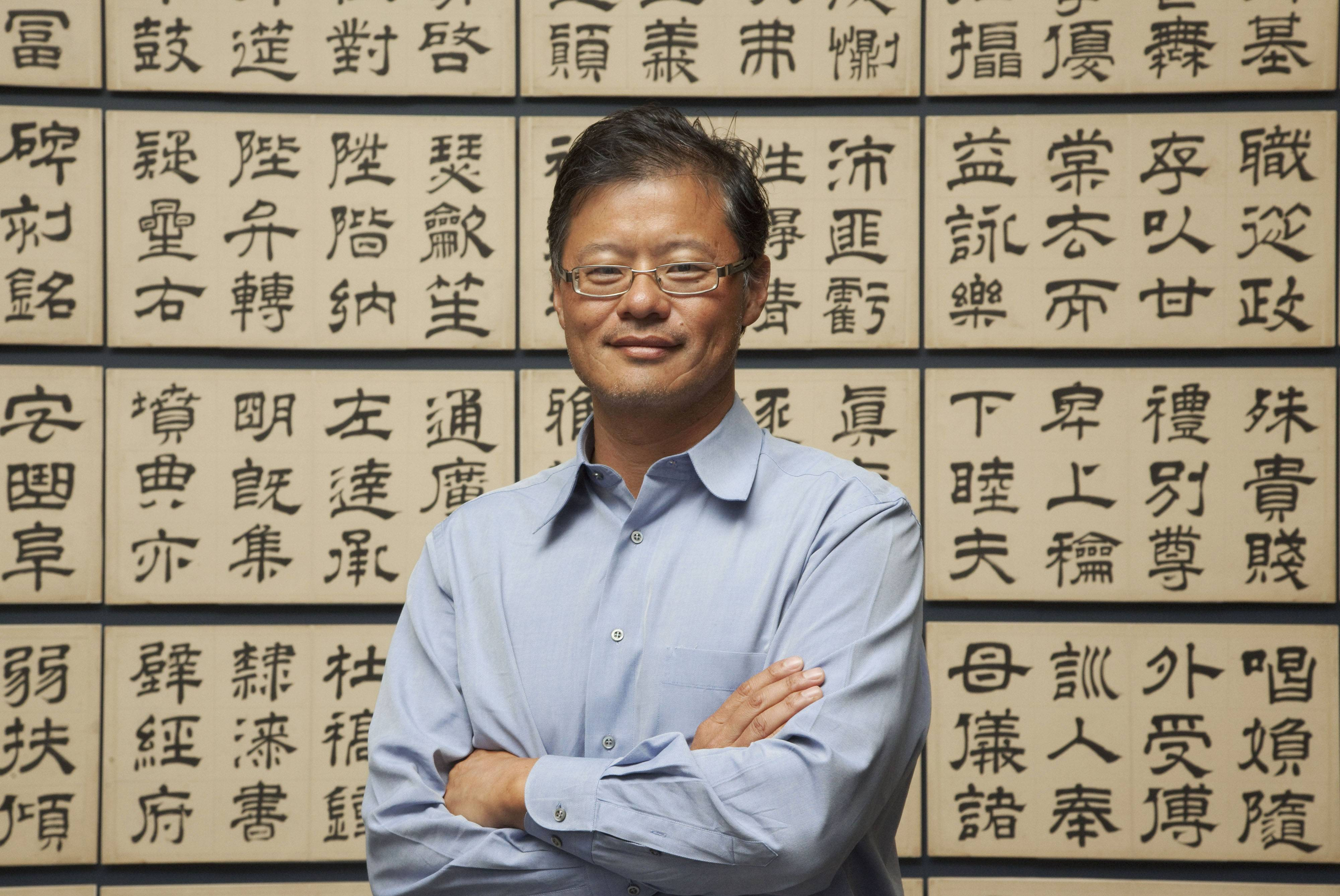 "Jerry Yang stands in front of ""The Thousand-Character Classic,"" by Wen Peng (1498-1573), an album of 85 double leaves with ink on paper. ""The Out of Character: Decoding Chinese Calligraphy — Selections From the Collection of Akiko Yamazaki and Jerry Yang"" exhibition runs until Aug. 17 at The Metropolitan Museum of Art in New York."