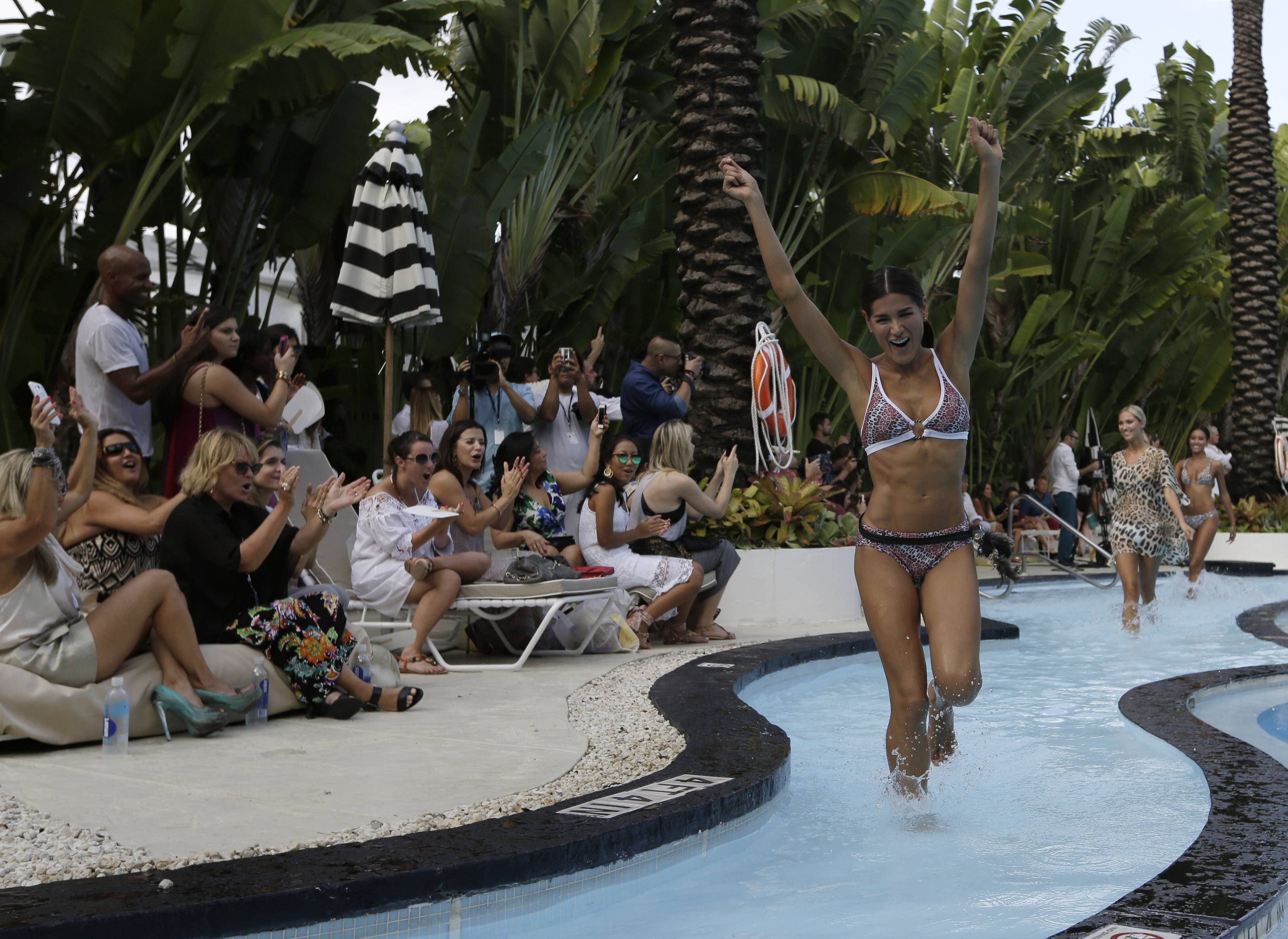 Models walk in a pool wearing swimwear designed by Poko Pano during the Mercedes-Benz Fashion Week Swim show Frida in Miami Beach, Fla.