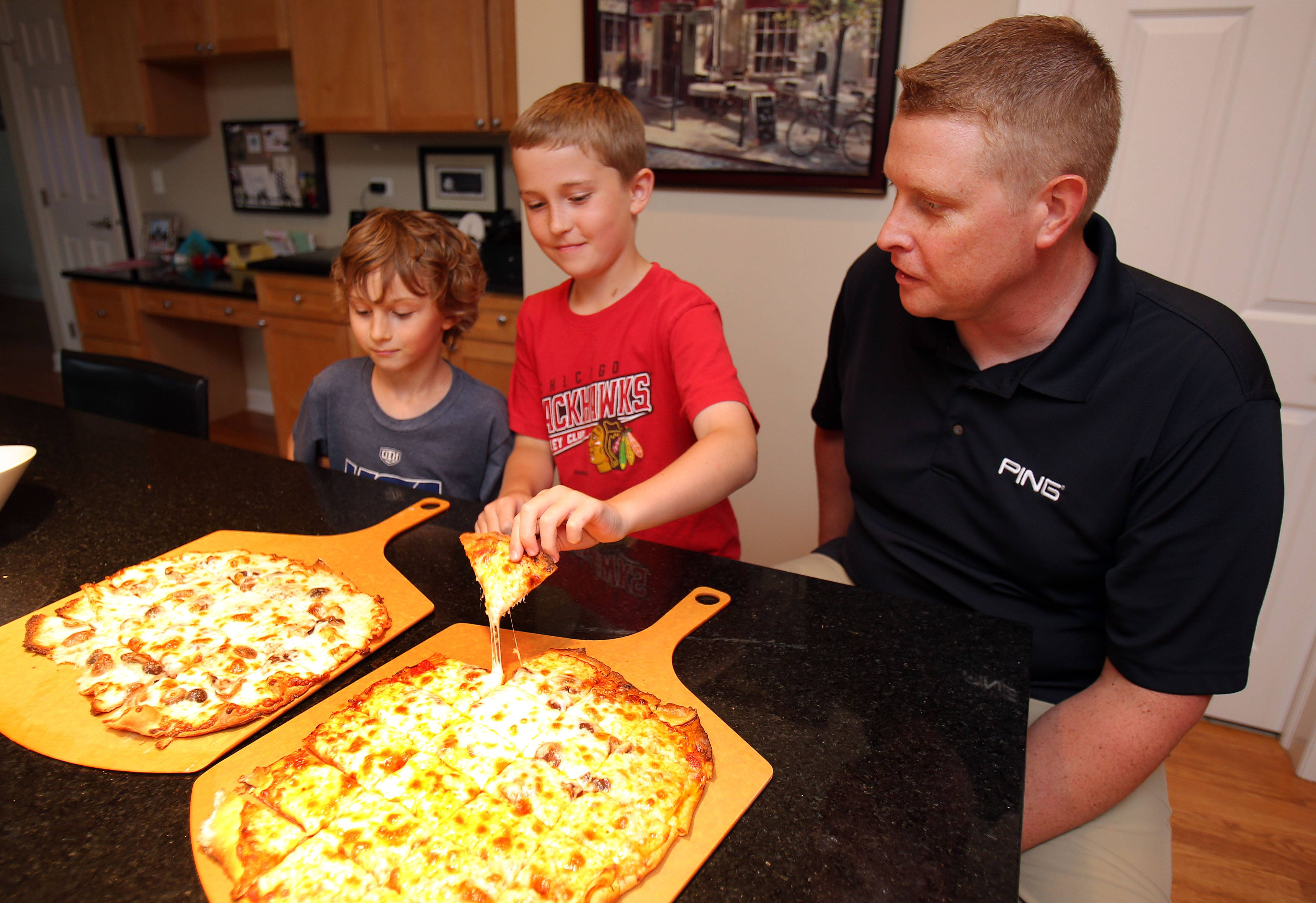 Shawn Schatteman, right, enjoys homemade pizza with his son, Blake, and neighbor Will Bosholdat. Schatteman makes his pizza dough from scratch.