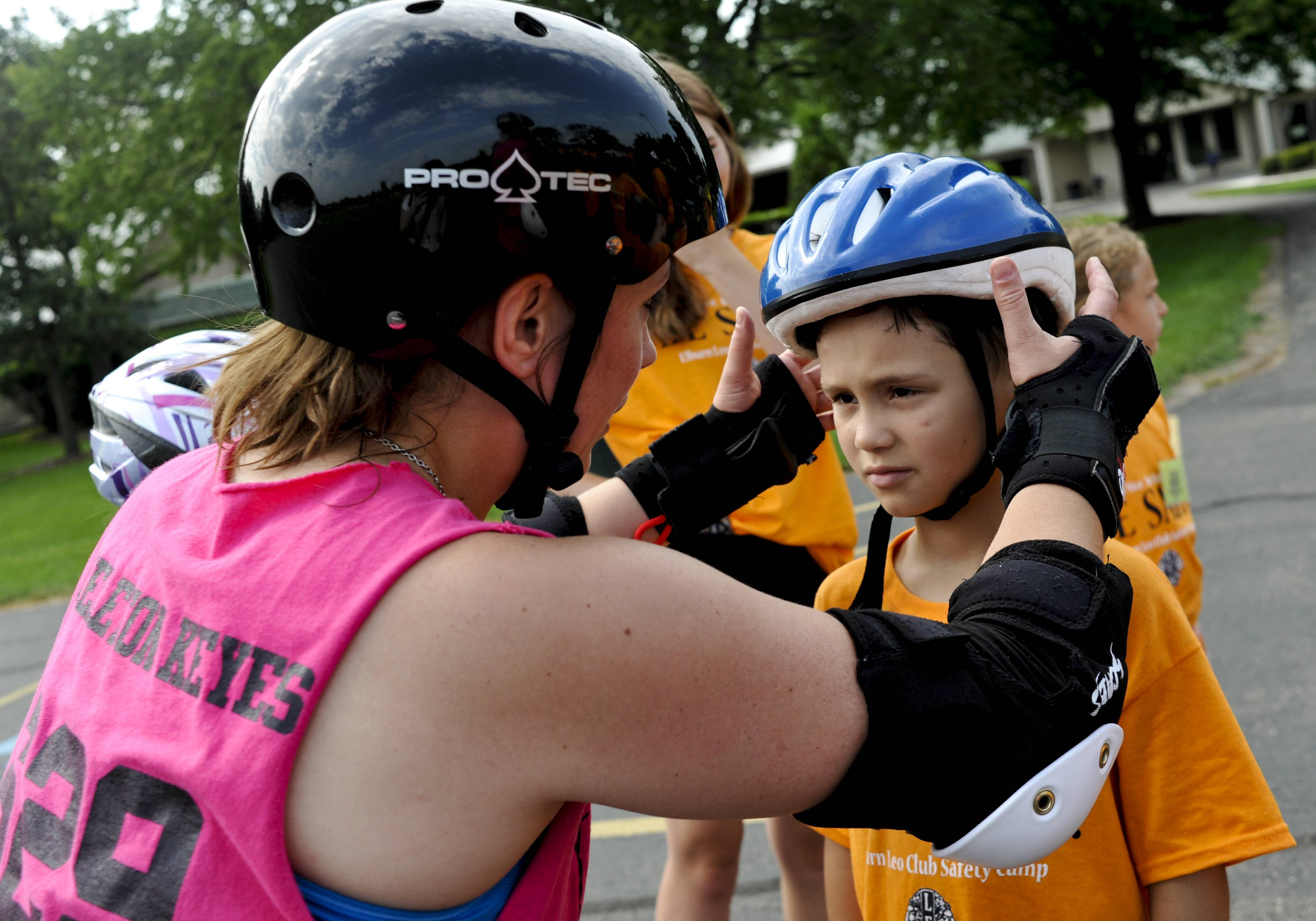 "Katherine ""Skeleton"" Keyes of the Barbed Wire Betties, DeKalb's Roller Derby League, fits a helmet on Vinnie Ridolfi, 7, of Aurora during the Safety Camp for Kids at Elburn Lions Club on Tuesday. The two-day camp was free for kids ages 7-10 and taught them about how to stay safe in a variety of situations, including roller skating."
