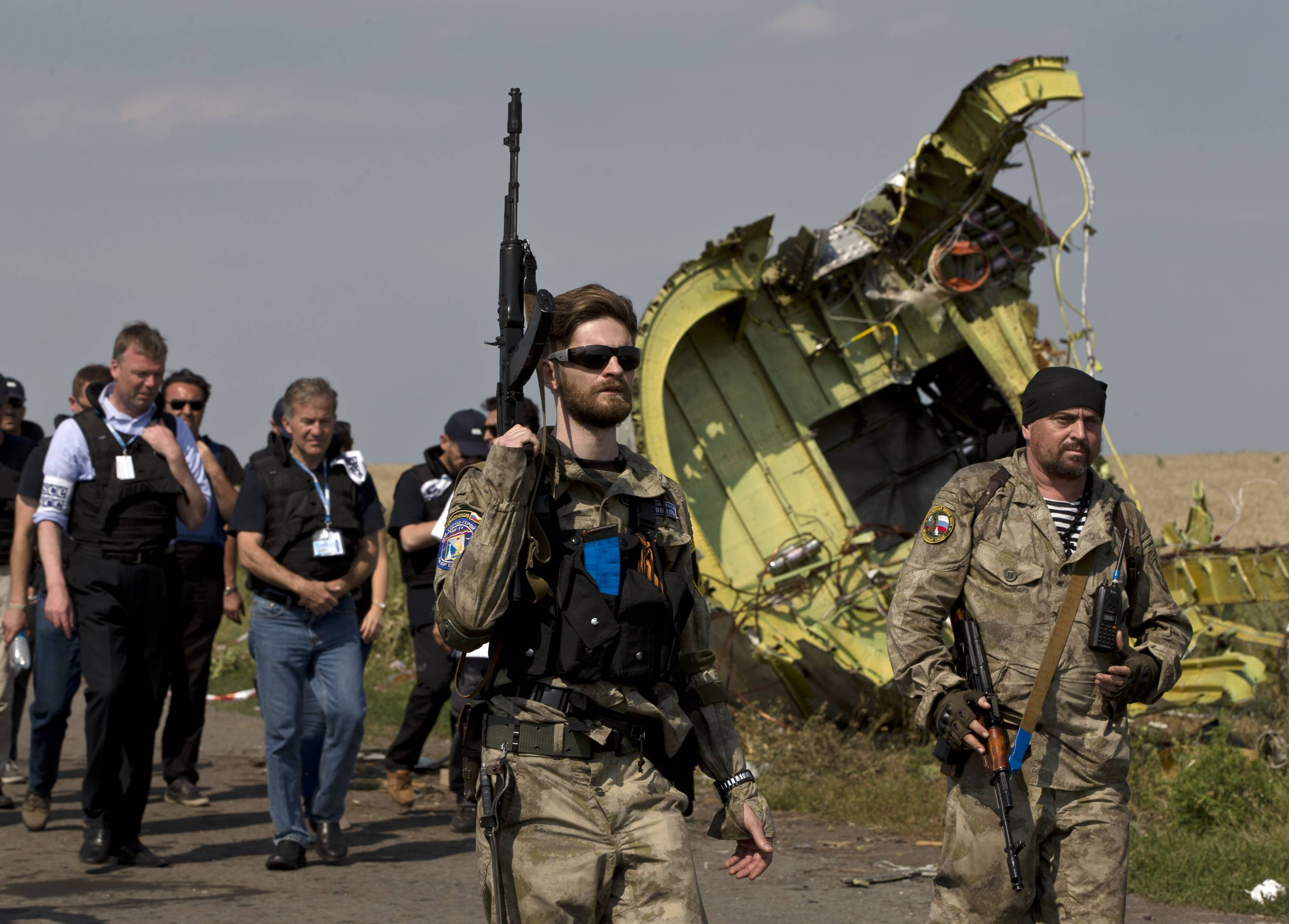 A pro-Russian rebel holds a gun passing by plane wreckage as members of the OSCE mission to Ukraine arrive for a media briefing at the crash site of Malaysia Airlines Flight 17, near the village of Hrabove, eastern Ukraine, Tuesday. A team of Malaysian investigators visited the site along with members of the OSCE mission in Ukraine for the first time since the air crash last week.