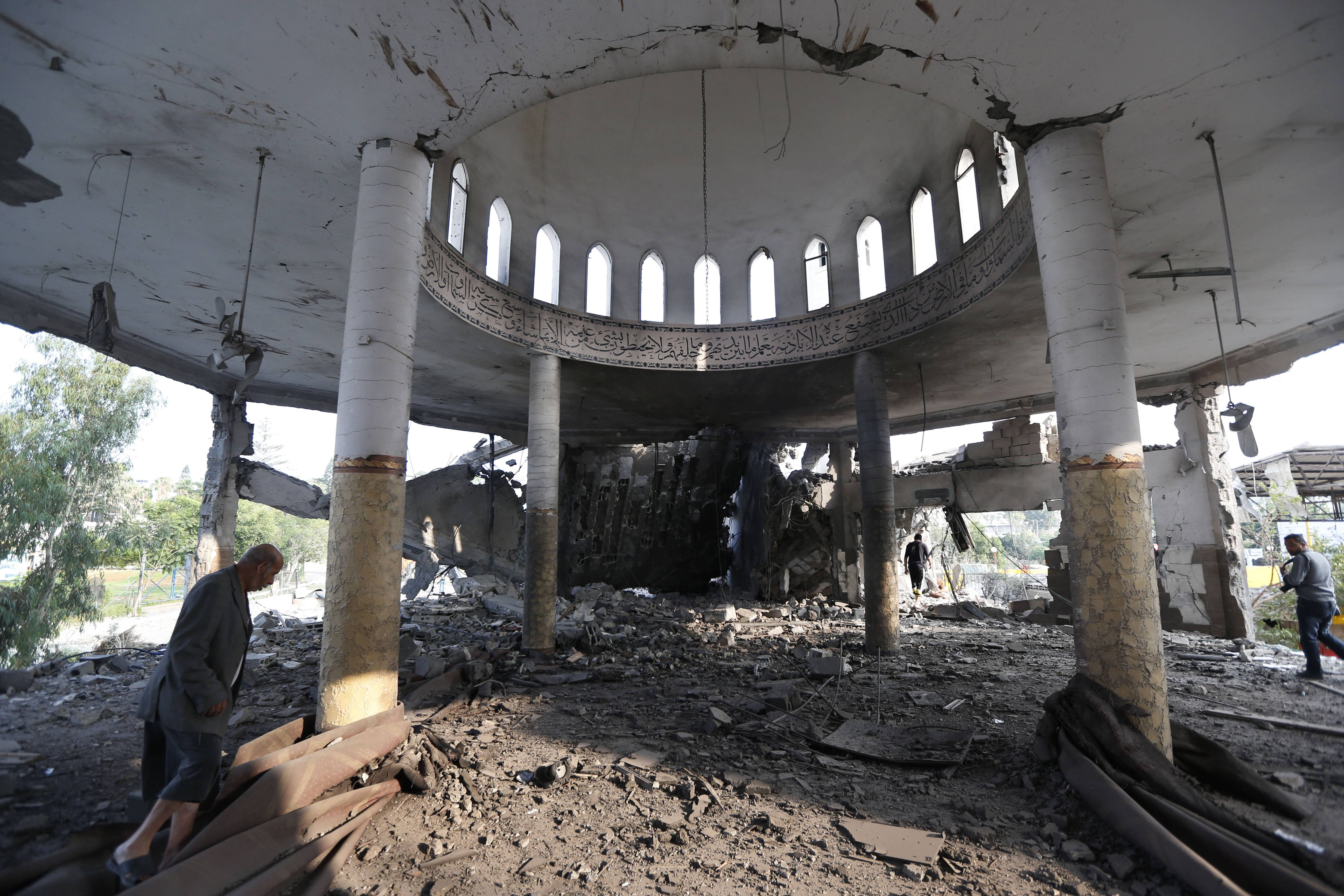 Khaled Sharmi, 67, left, walks inside the Al Aqsa Martyrs mosque destroyed by an overnight Israeli strike in Gaza City Tuesday. Israel bombed five mosques, a sports stadium and the home of the late Hamas military chief across the Gaza Strip early on Tuesday, a Gaza police official said.