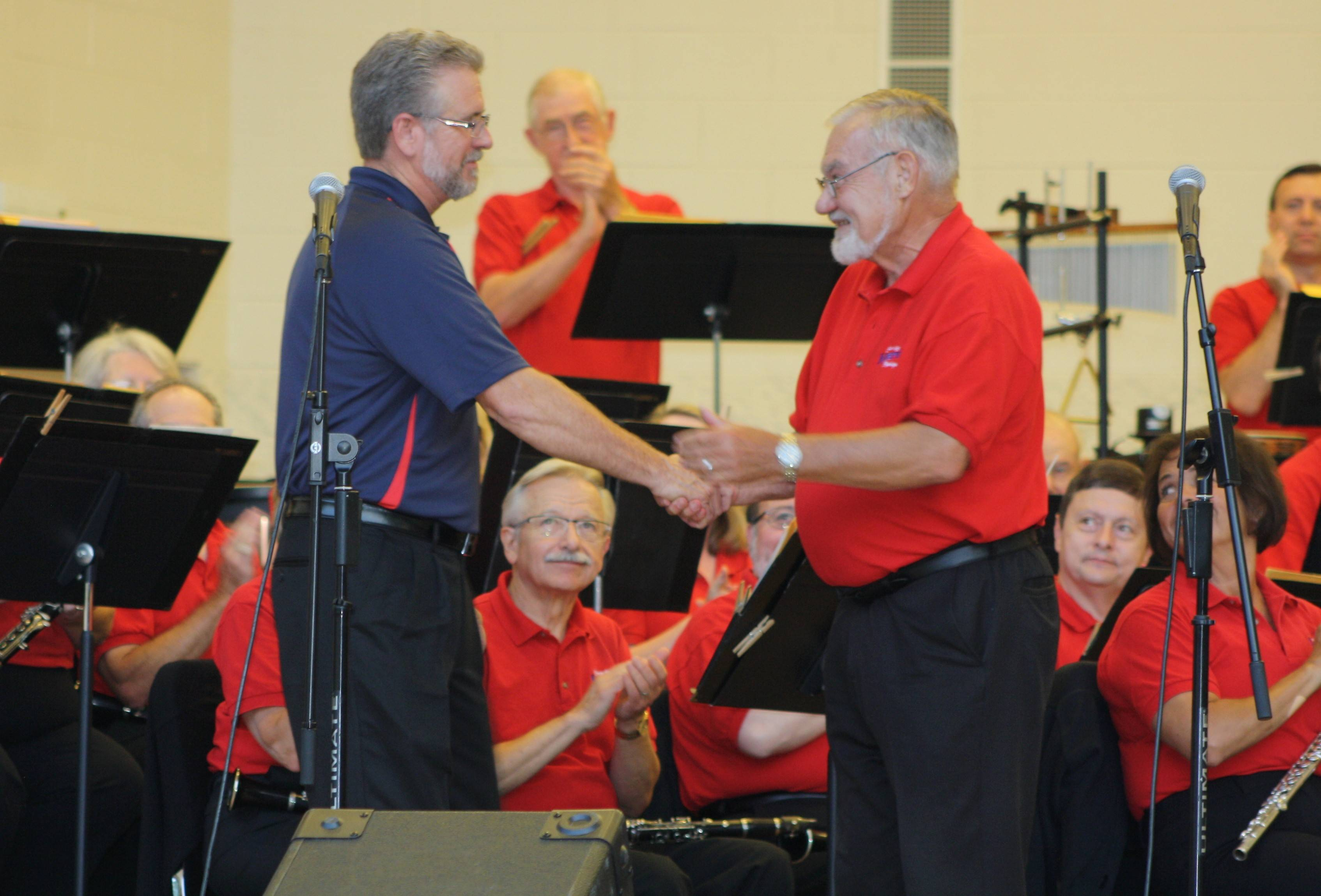 Bruce Beach, left, president-elect of the Texas Bandmasters Association, congratulates Ron Keller, director of the Naperville Municipal Band, on being invited to perform at the prestigious Texas Bandmasters Association convention in 2015.