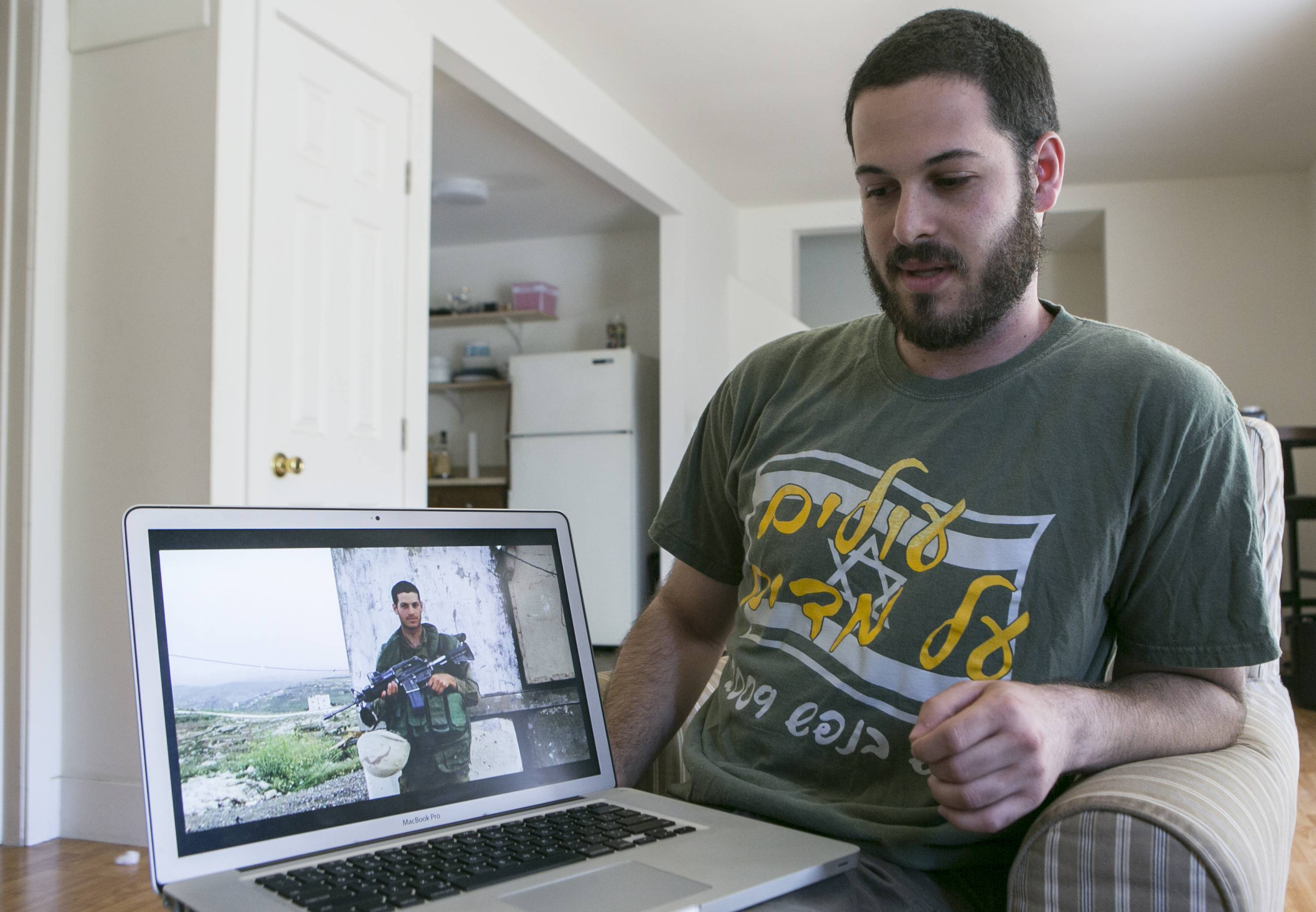 Mike Fishbein, a U.S.-born soldier from Los Angeles who fought for the Israel Defense Forces with a photo of himself from when he served in the IDF.