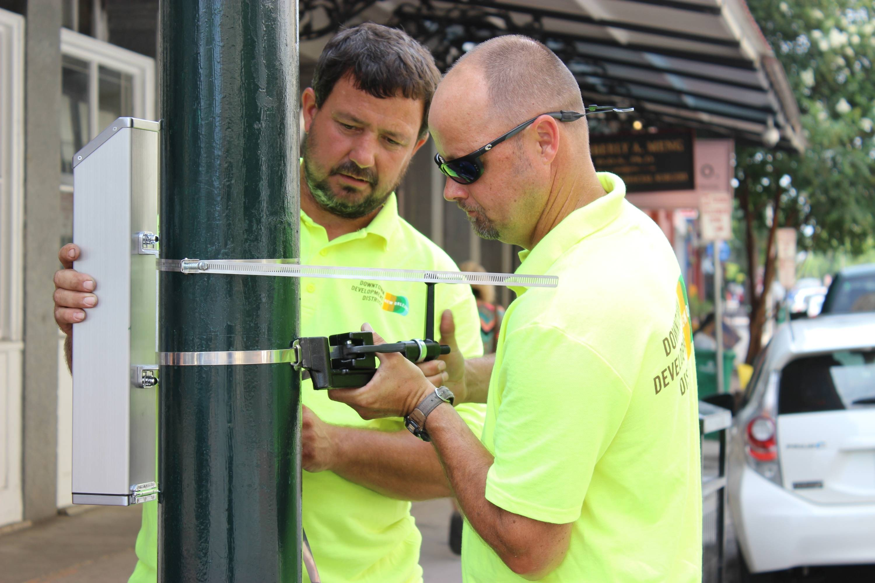 Dale Alvin, right, tightens the strap holding a cigarette butt recycling container to a lamp post in New Orleans' Warehouse District.