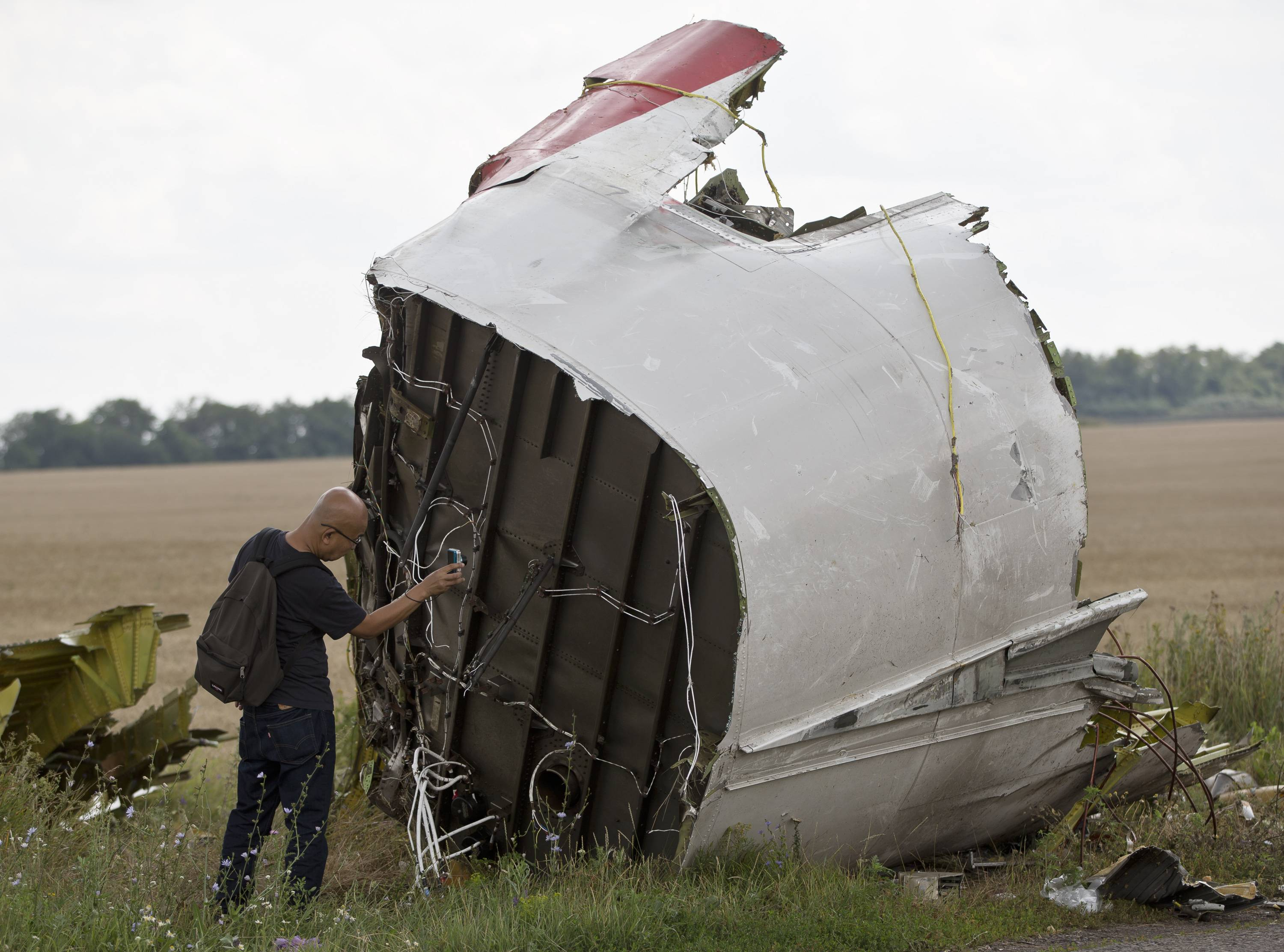 "A Malaysian air crash investigator takes pictures of wreckage at the crash site of Malaysia Airlines Flight 17 near the village of Hrabove, eastern Ukraine, Tuesday. Senior U.S. intelligence officials said Tuesday that Russia was responsible for ""creating the conditions"" that led to the shooting down of the flight."