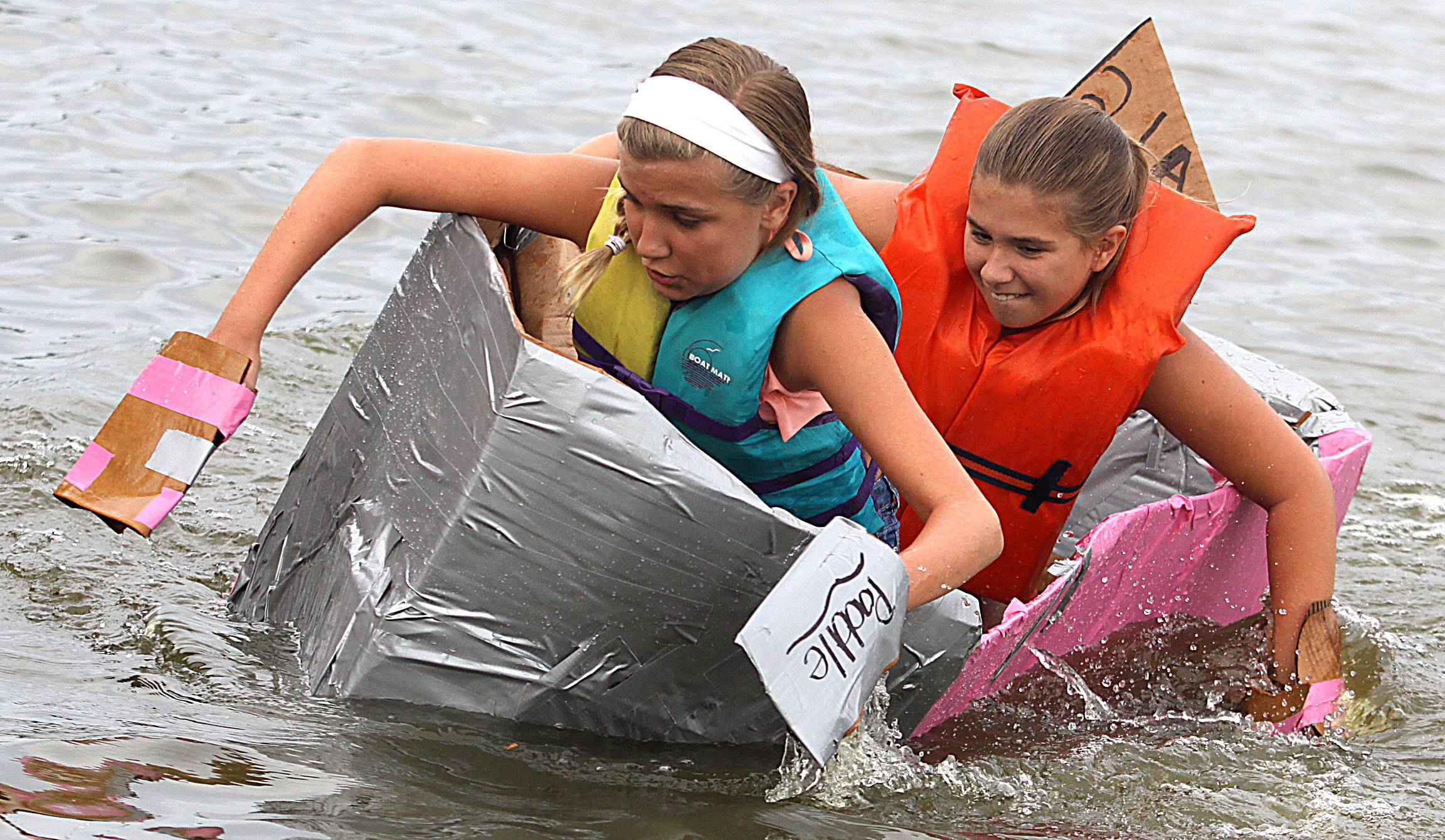 "Alaina Moran, 12, of Lake in the Hills, left, tries to keep the ""SS Starbucks"" craft afloat with her sister Alyssa, 9, during the Cardboard Boat Regatta juniors race as part of Algonquin Founders' Days festivities on the Fox River."