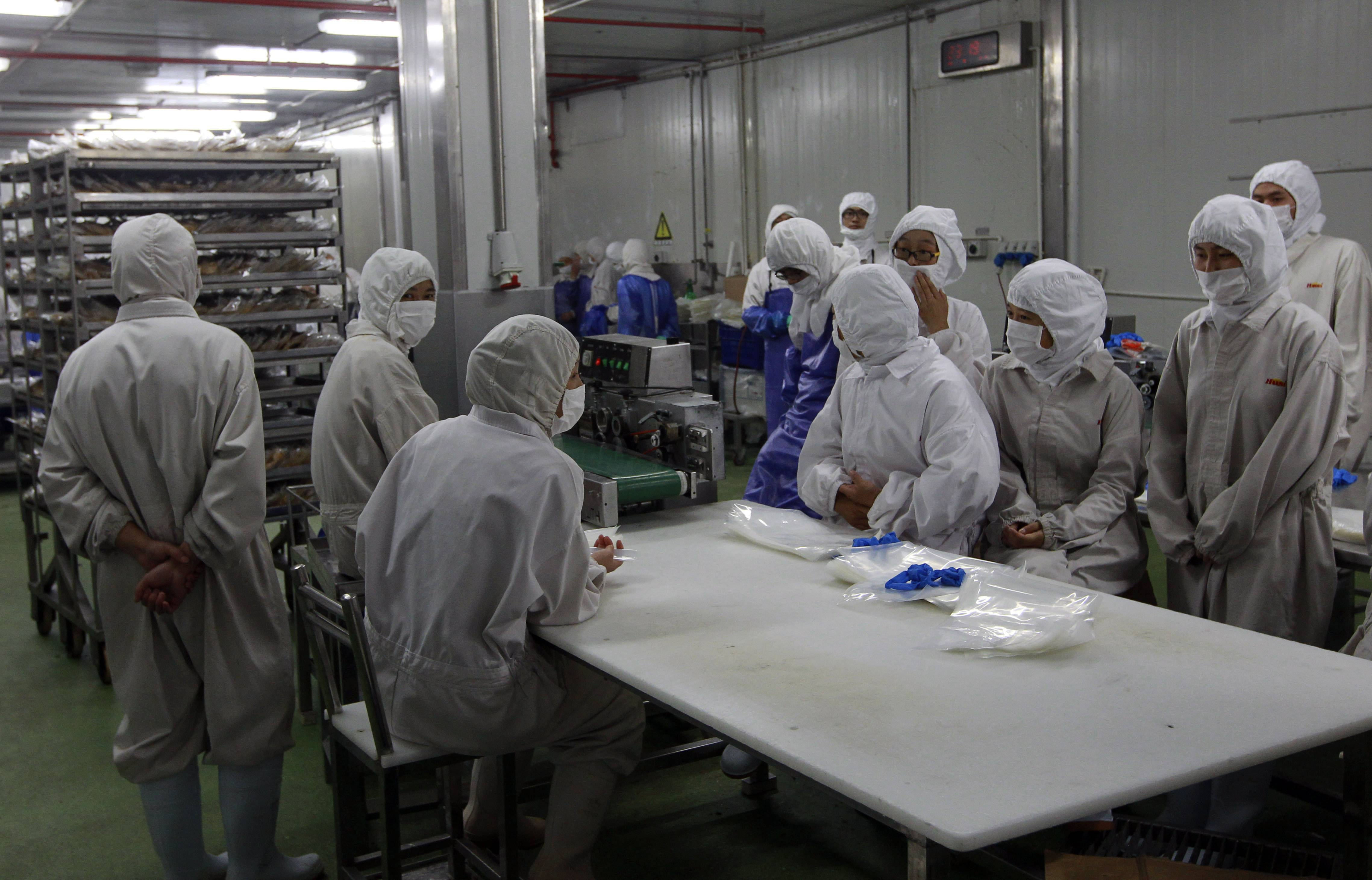 In this July 20 photo released by China's Xinhua News Agency, workers gather while they have nothing to do at the workshop of Shanghai Husi Food Co., a meat supplier for McDonald and KFC, in Shanghai, China. A suspect meat scandal in China engulfed Starbucks and Burger King on Tuesday and spread to Japan where McDonald's said the Chinese supplier accused of selling expired beef and chicken had provided 20 percent of the meat for its chicken nuggets.