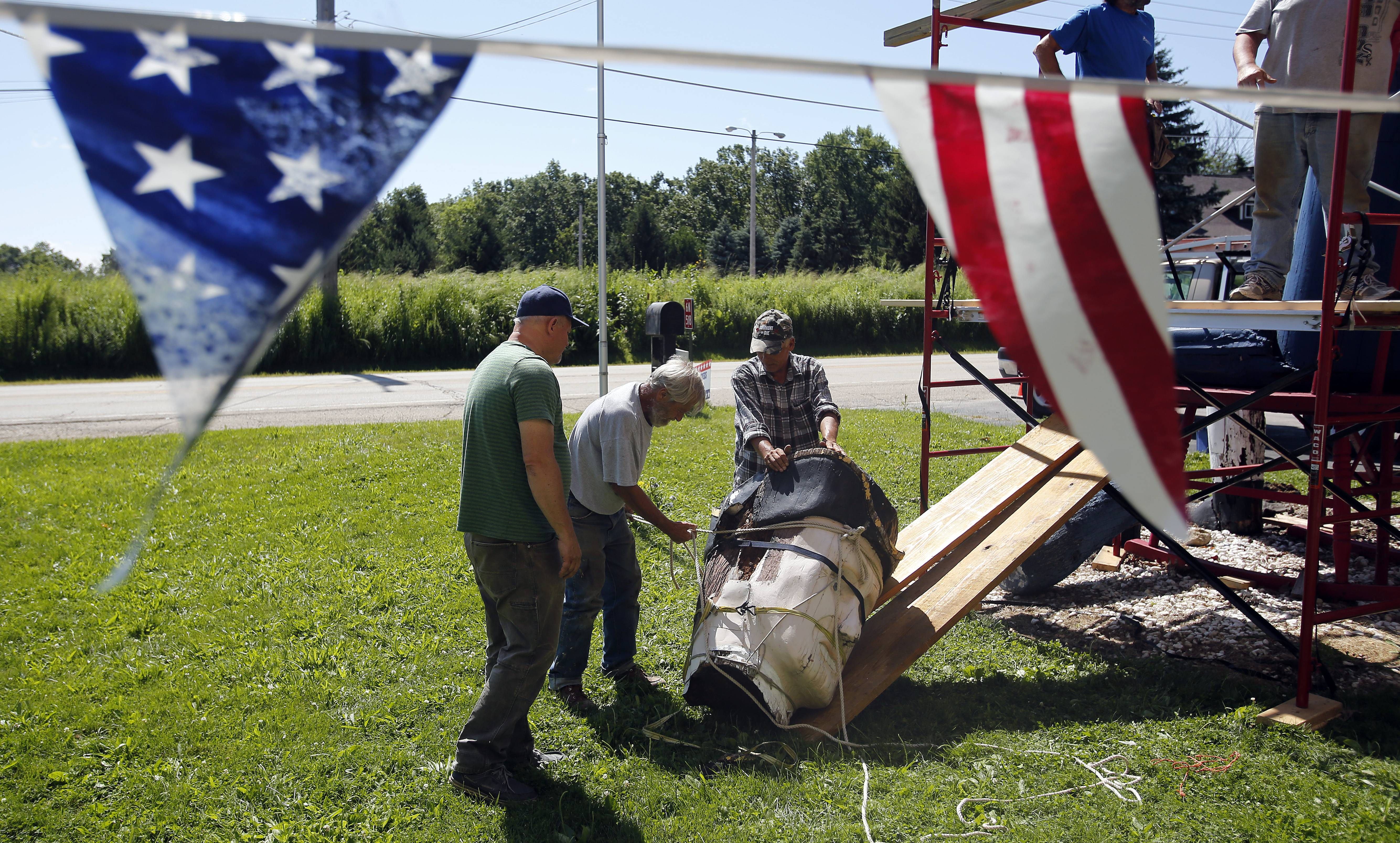 Clint Carey, left, of Pingree Grove has bought the 25-foot-tall wood sculpture of Revolutionary War soldier that's been on display since 1976 on the front lawn of Custom Furniture in St. Charles.