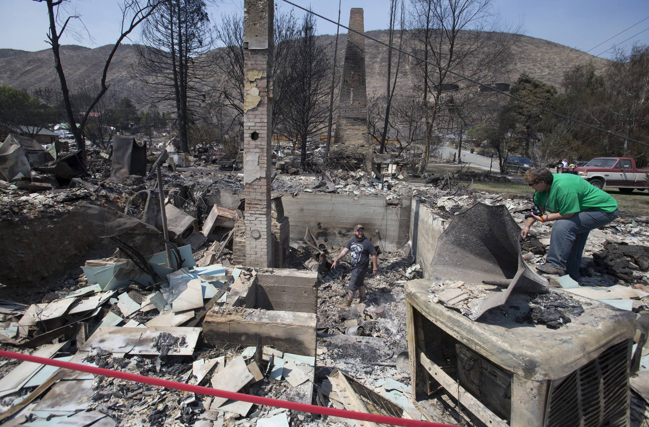 Jake Hixon and Kathy Harding look for family heirlooms they may have been spared at a relative's house after the fire that swept through Pateros, Wash., last Thursday.
