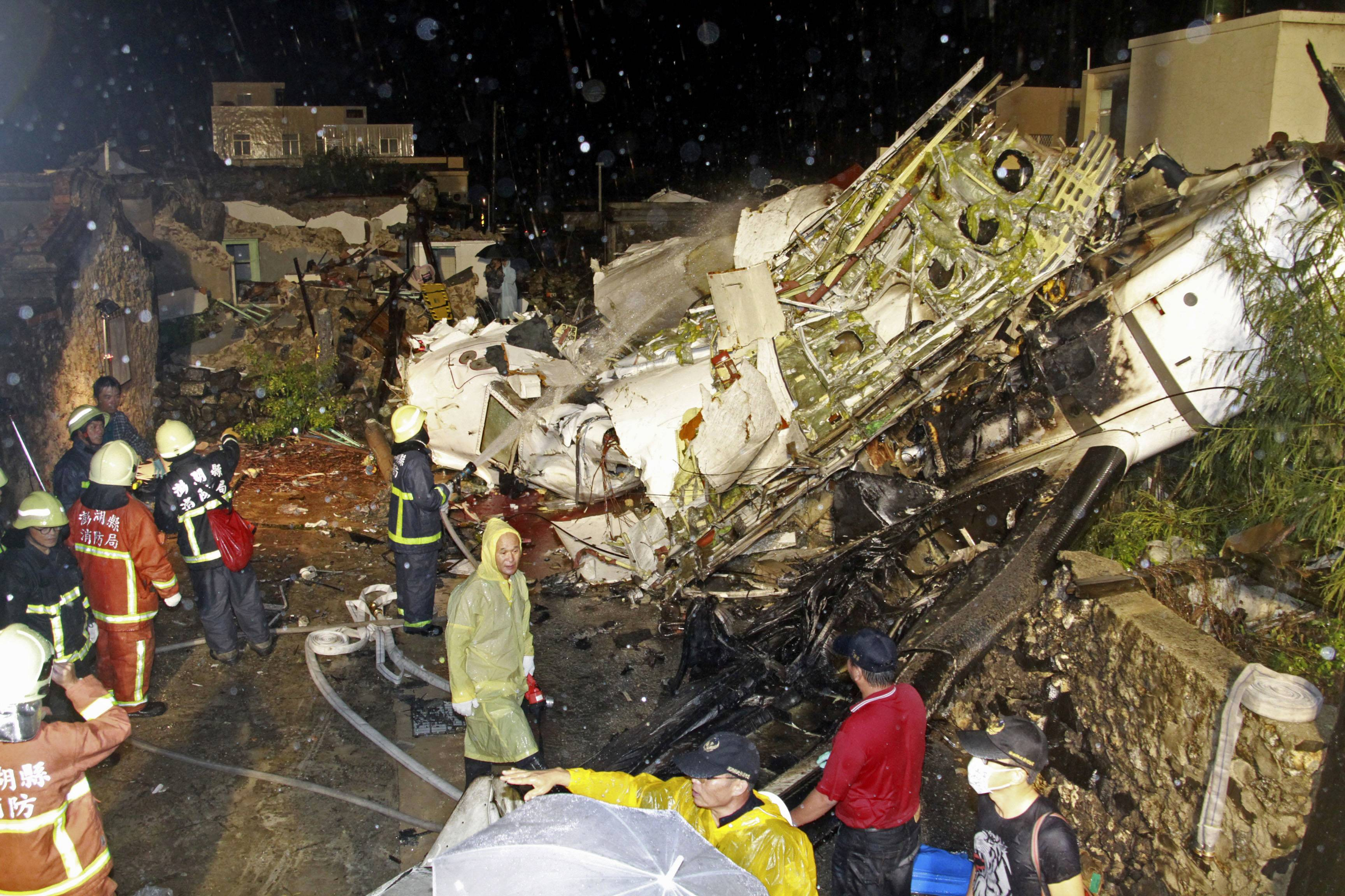 Rescue workers work next to the wreckage of TransAsia Airways flight GE222 which crashed while attempting to land in stormy weather on the Taiwanese island of Penghu, late Wednesday, killing 47 people and wrecking houses and cars on the ground.