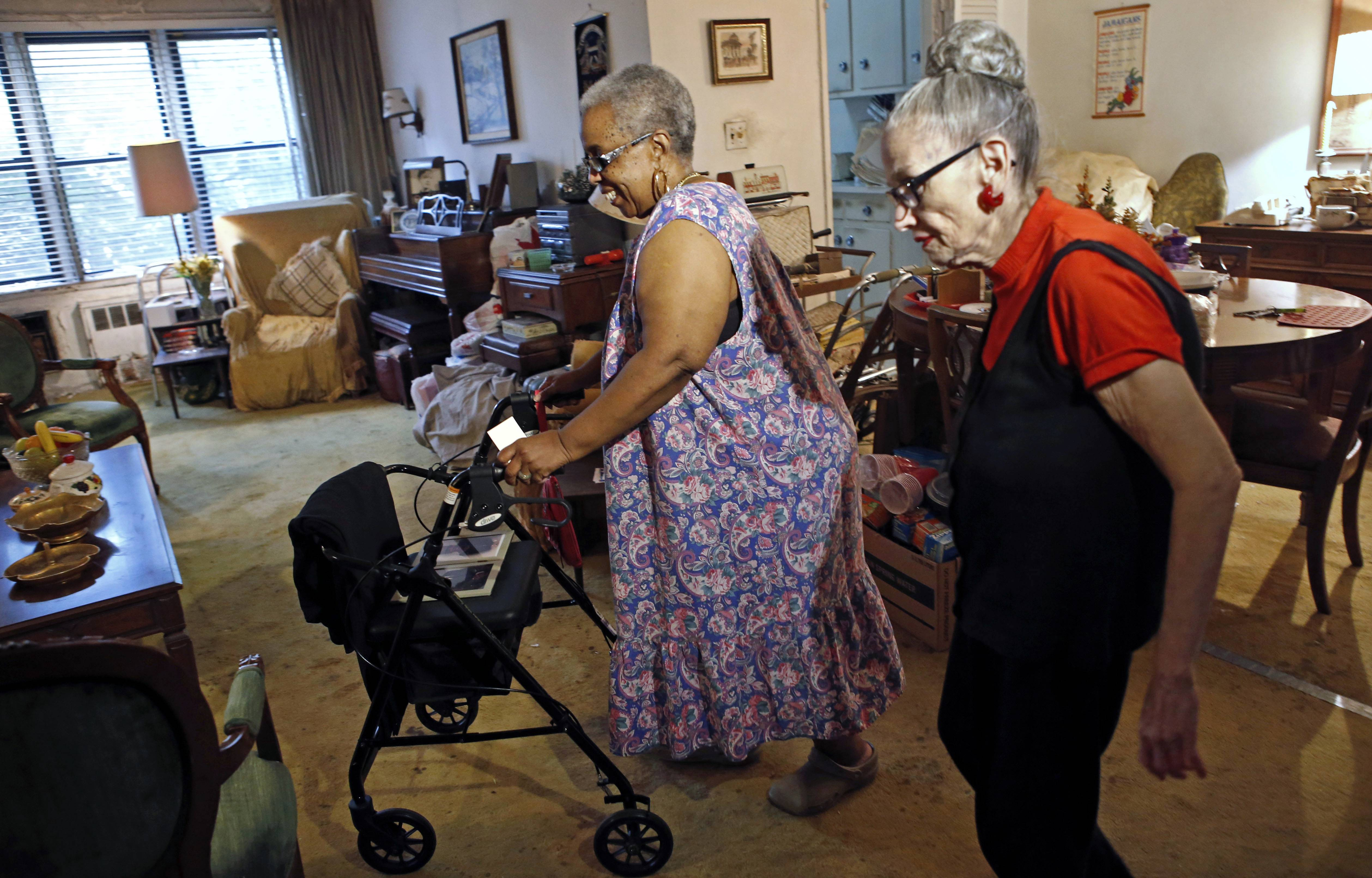 Carolyn Allen, left, a 69-year-old widow who has suffered two strokes, makes her way to the living room with roommate Marcia Rosenfeld, who owns the apartment Allen lives in New York. The two women are roommates thanks to a home-sharing program run by a New York-based nonprofit agency.