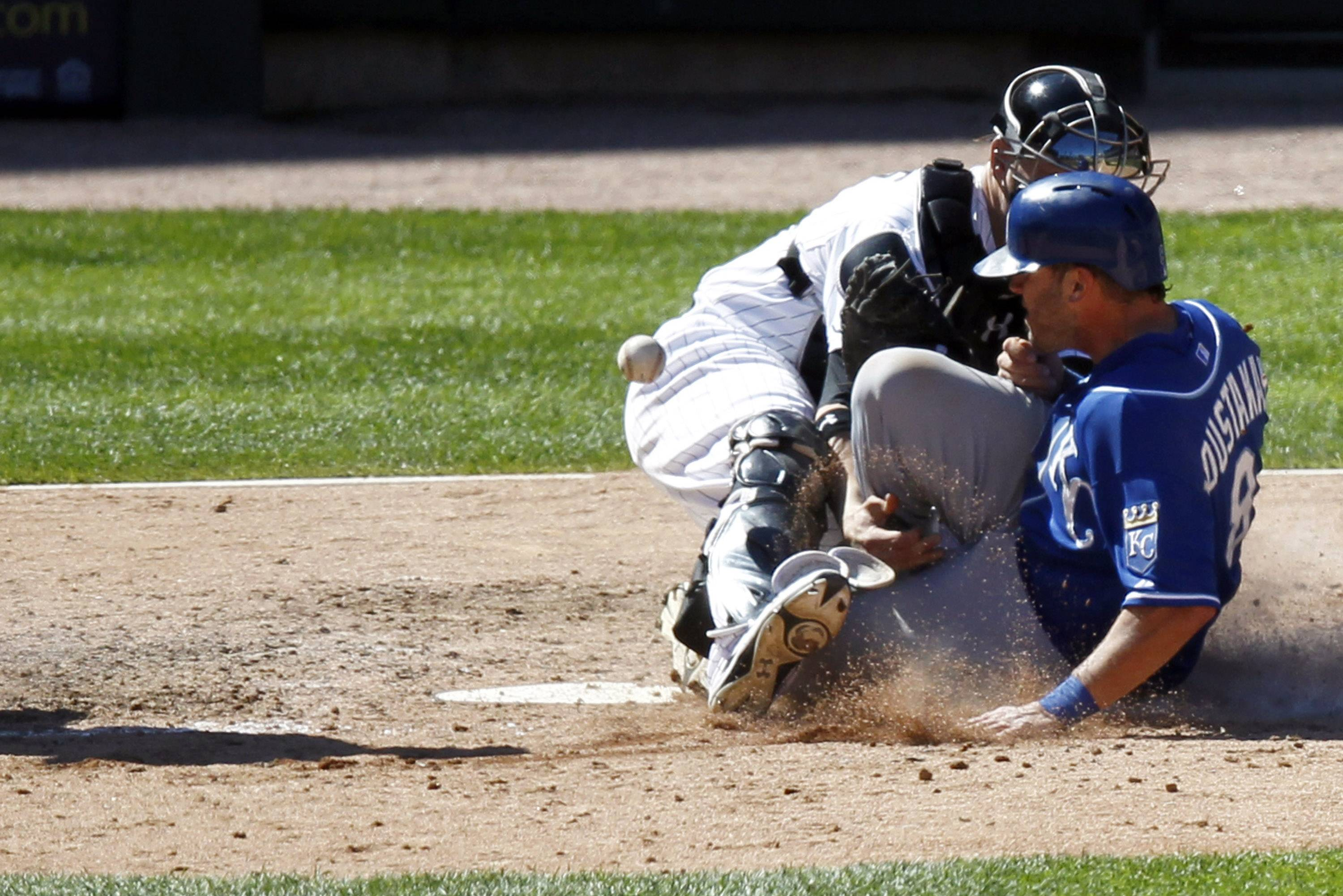 White Sox catcher Tyler Flowers, left, attempts to tag out Kansas City Royals' Mike Moustakas at the plate during the ninth inning of a baseball game on Wednesday, July 23, 2014, in Chicago.
