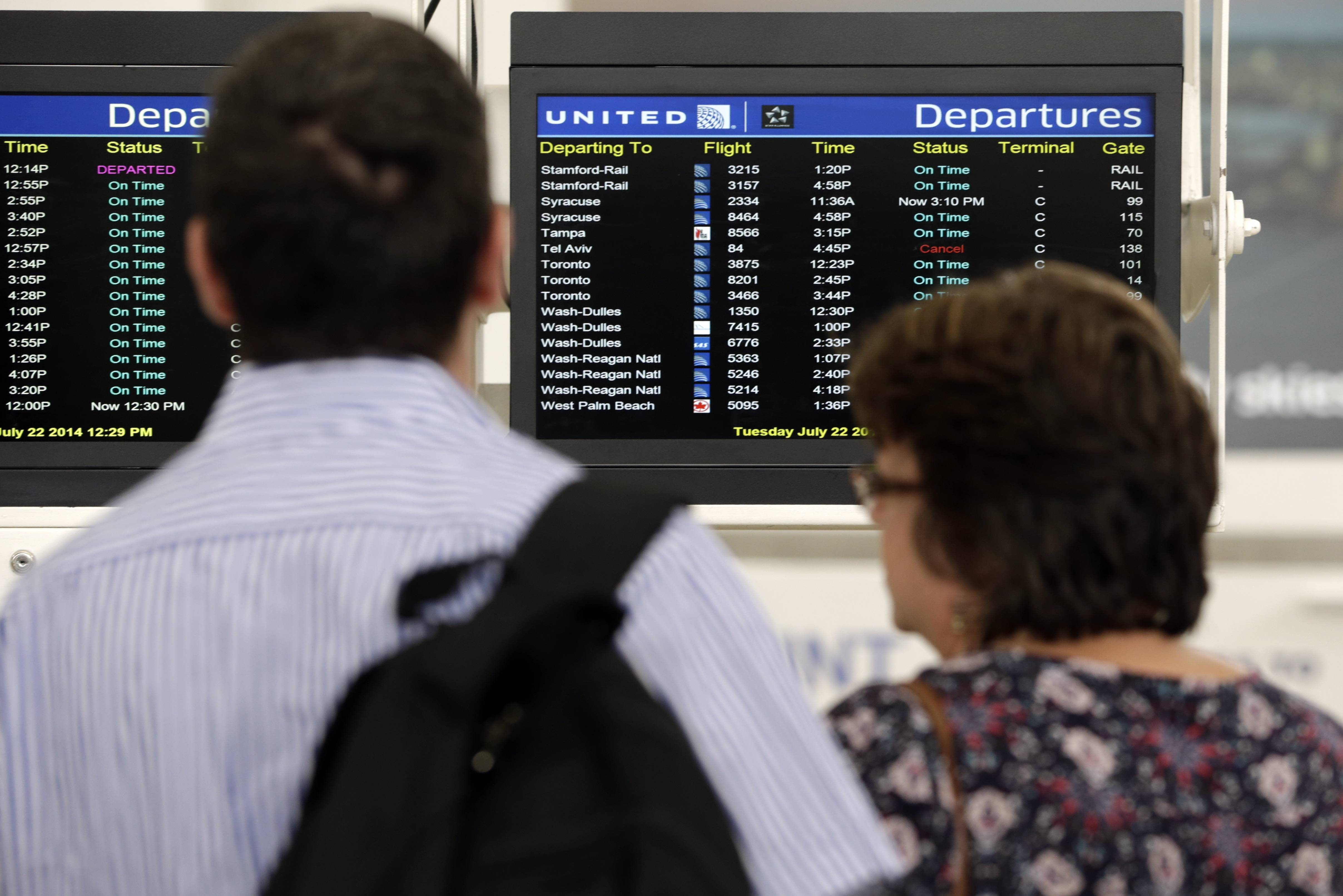 Travelers congregate in front of a departures board showing one canceled flight to Tel Aviv at Newark Liberty International Airport.