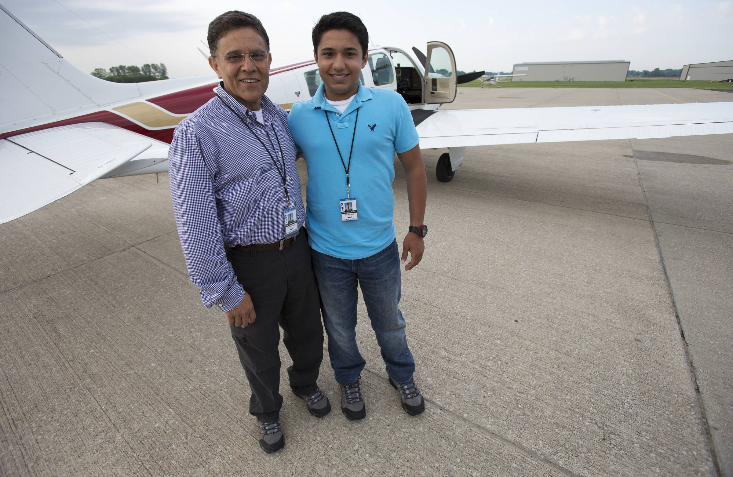 Babar Suleman and son, Haris Suleman, 17, stand next to their plane at an airport in Greenwood, Ind., June 19, before taking off for an around-the-world flight. Their single-engine plane crashed in waters off American Samoa on Wednesday.
