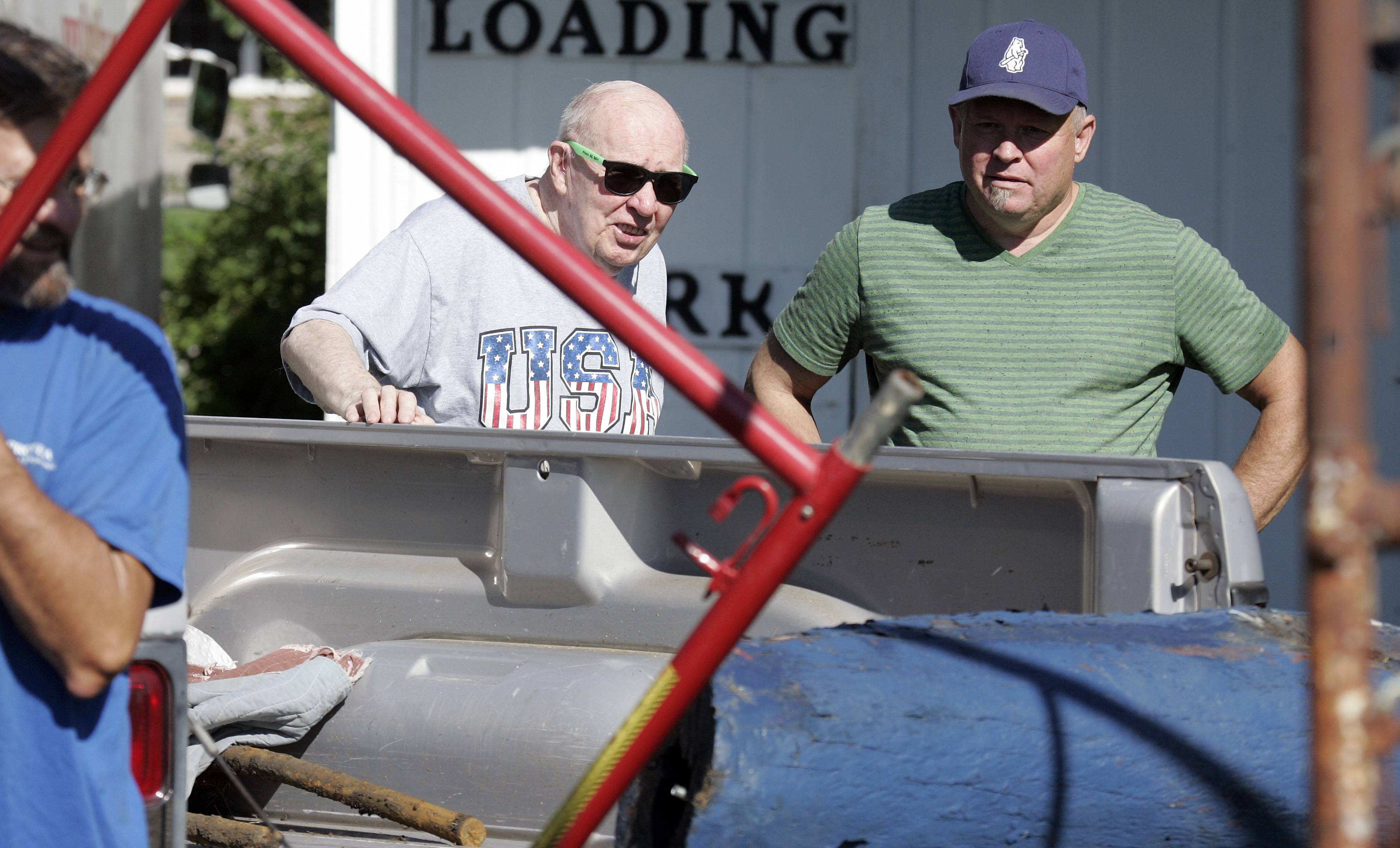 Previous owner Richard Pakan, of Custom Furniture left, and Clint Carey of Pingree Grove watch as the 25-foot-tall wood sculpture of Revolutionary War soldier that's been on display since 1976 on the front lawn of Custom Furniture in St. Charles is dismantled Wednesday.