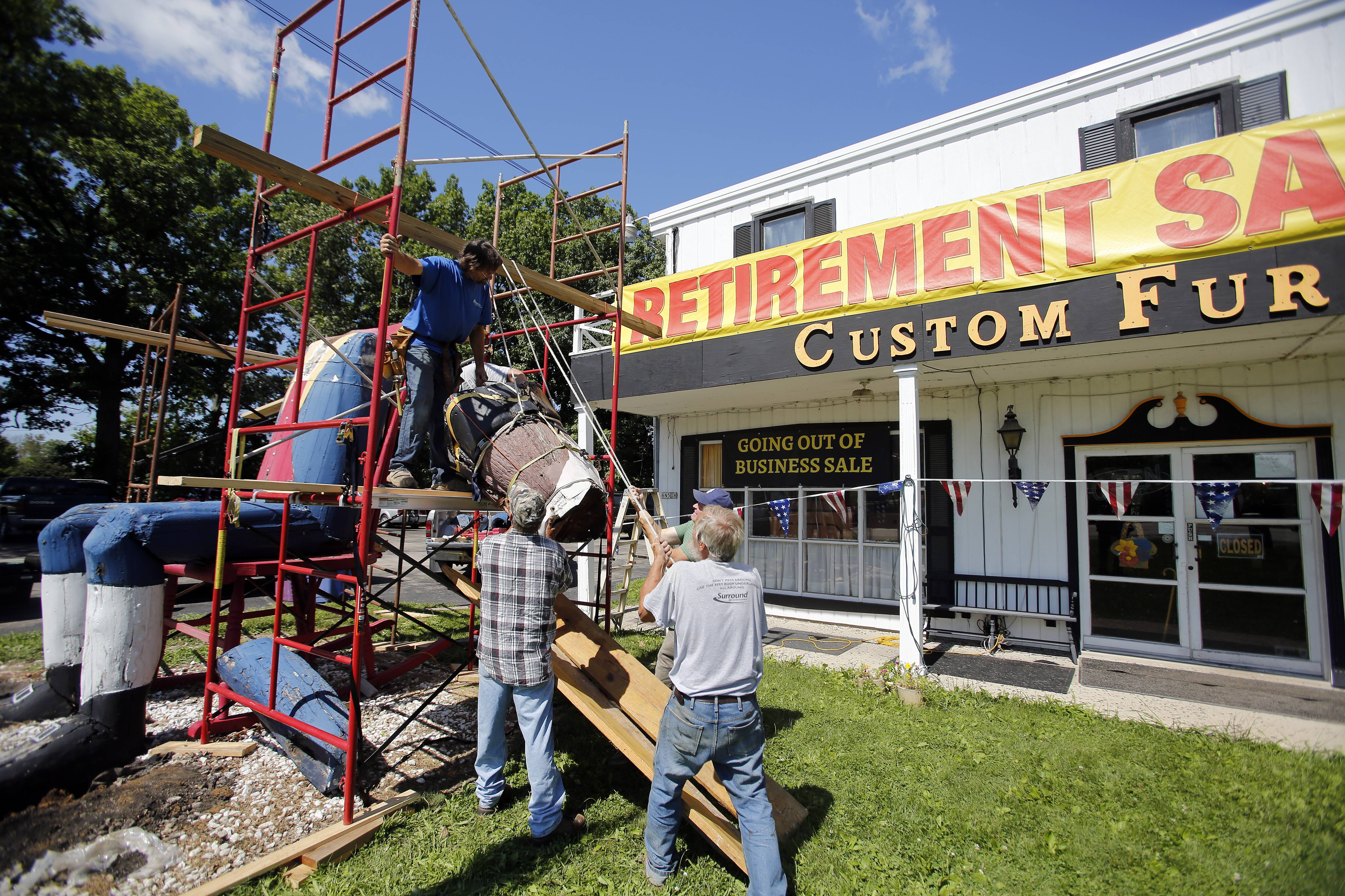 Workers lower the head Wednesday from the 25-foot-tall wood sculpture of Revolutionary War soldier at Custom Furniture in St. Charles.