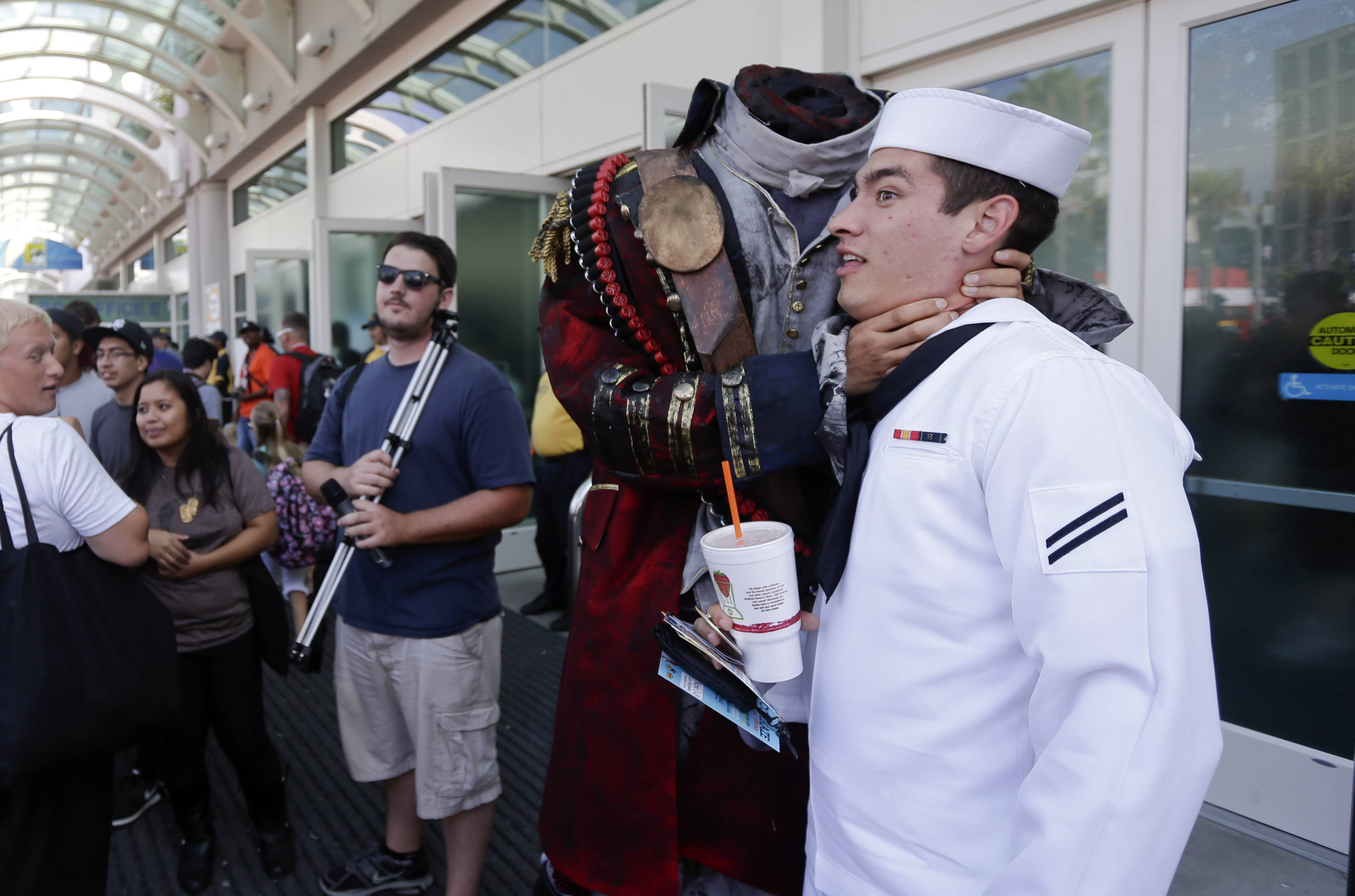 Navy Mineman Bradley Allred jokes as he has his picture taken with a headless character during Comic-Con, in San Diego last year.