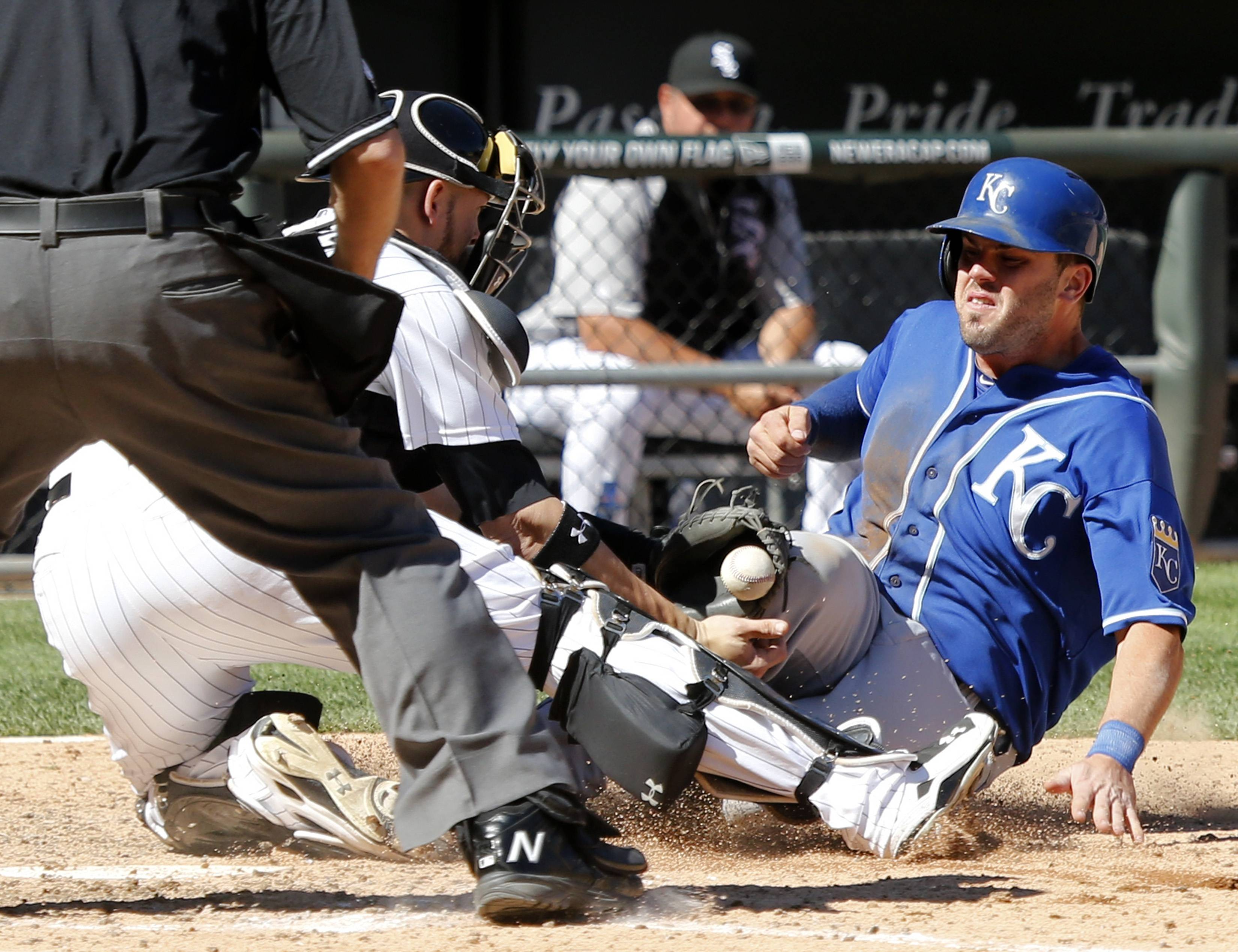 Kansas City Royals' Mike Moustakas knocks the ball out of the glove of Chicago White Sox catcher Tyler Flowers allowing Moustakas to score the winning run during the ninth inning of a baseball game on Wednesday, July 23, 2014, in Chicago.