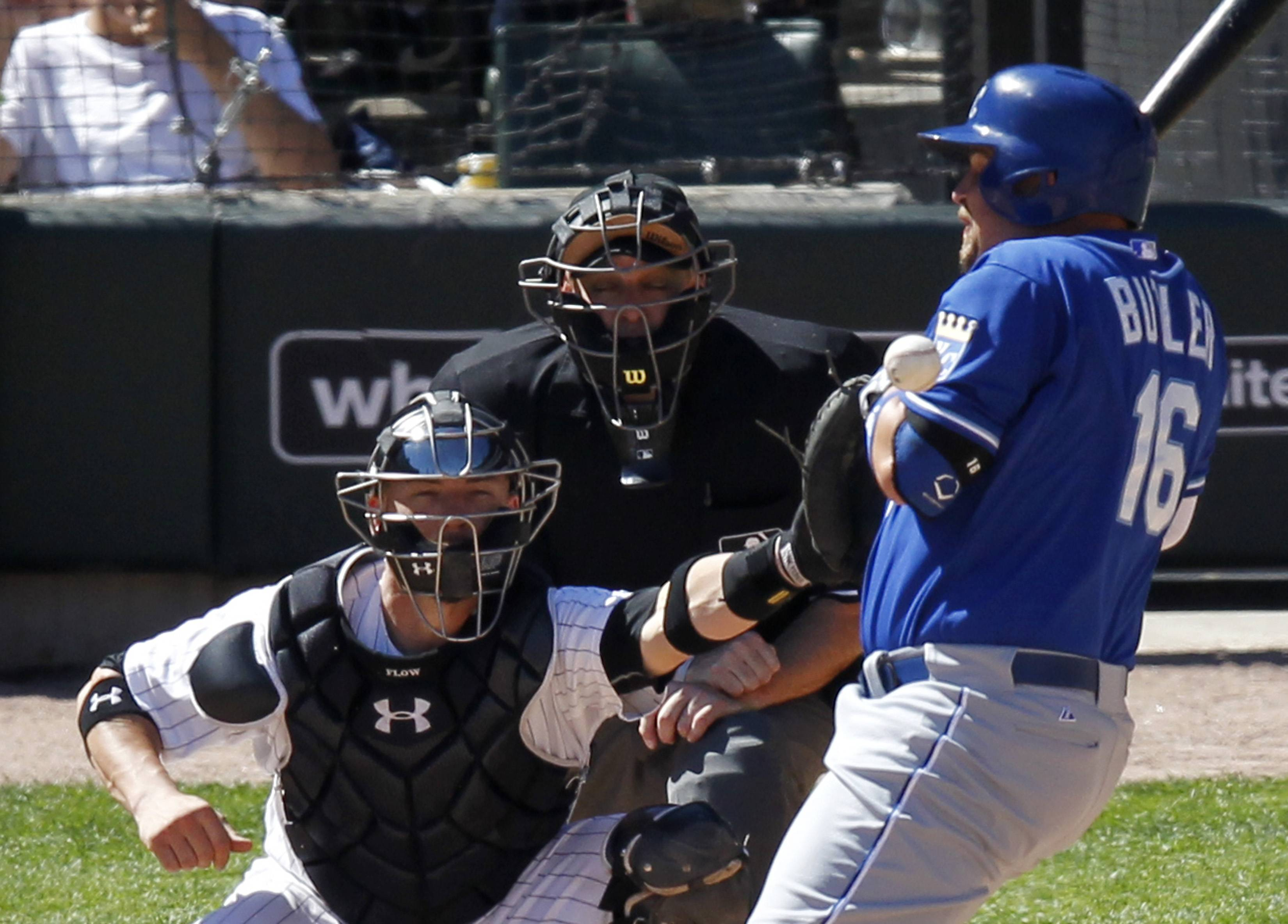 Kansas City Royals' pinch hitter Billy Butler gets hit by a ball from Chicago White Sox relief pitcher Ronald Belisario during the eighth inning of a baseball game Wednesday, July 23, 2014, in Chicago, as Sox catcher Tyler Flowers and home plate umpire Andy Fletcher look on.