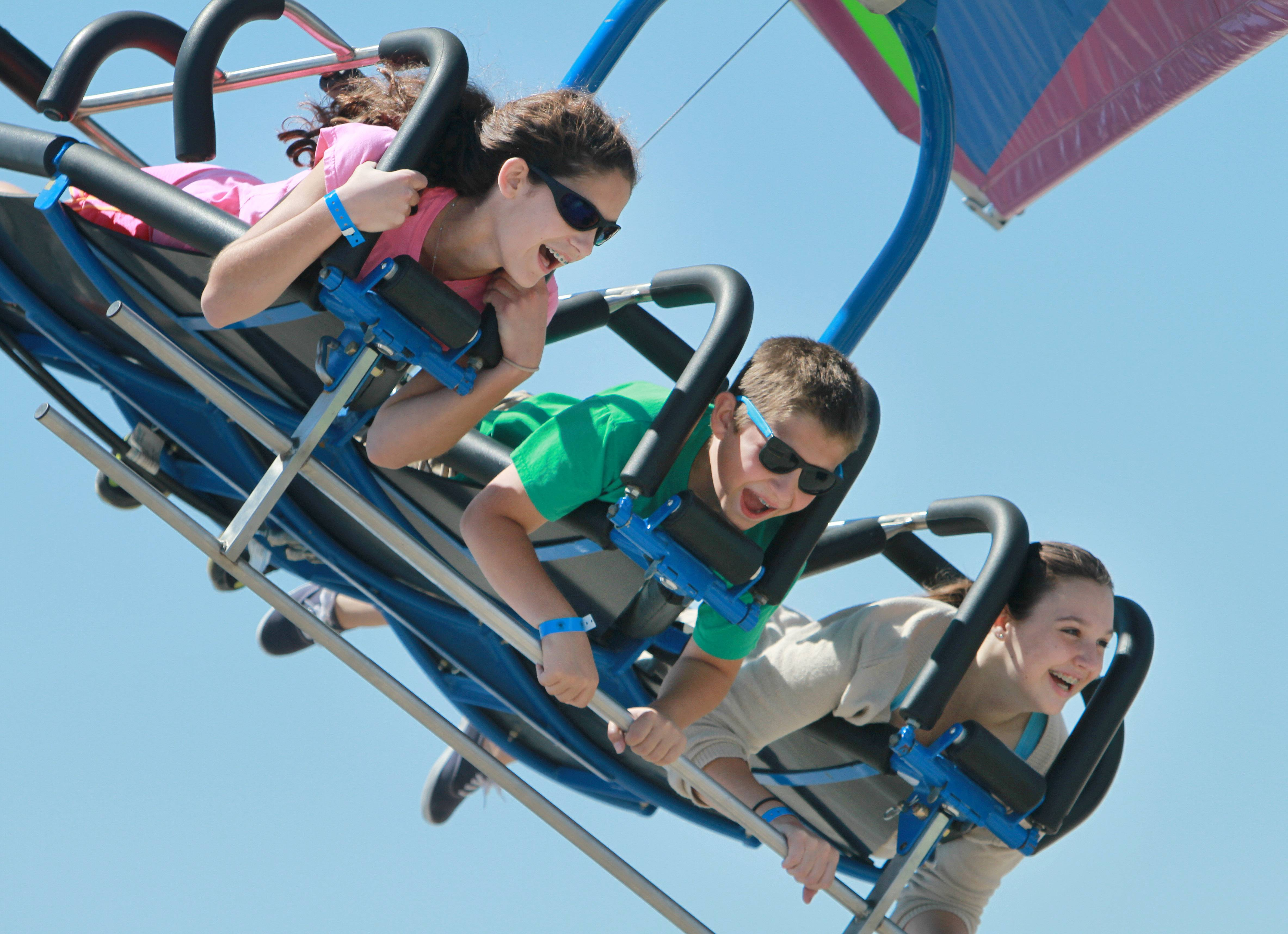 From left, Luna Ventura, 13, Enzo Ventura, 10, and Nora Maihack, 14, all of Grayslake, ride the Cliff Hanger Thursday at the Lake County Fair in Grayslake.