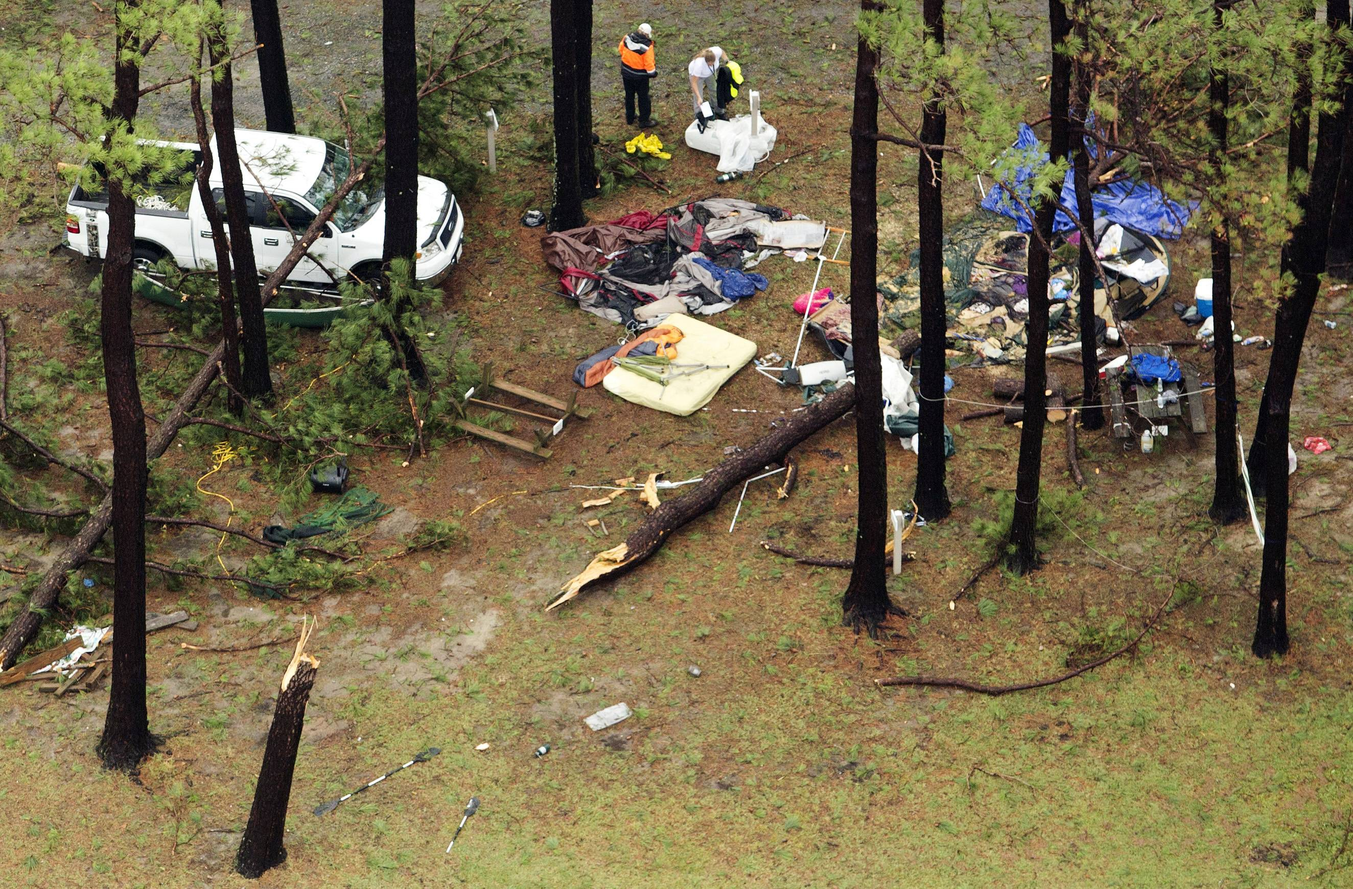 In this aerial photo, people inspect damage at Cherrystone Family Camping & RV Resort in Northampton County, Va., Thursday, after a severe storm swept through the area. Softball-sized hail and rain toppled dozens of trees and flipped recreational vehicles at the campground Thursday, killing two people and injuring more than two dozen.