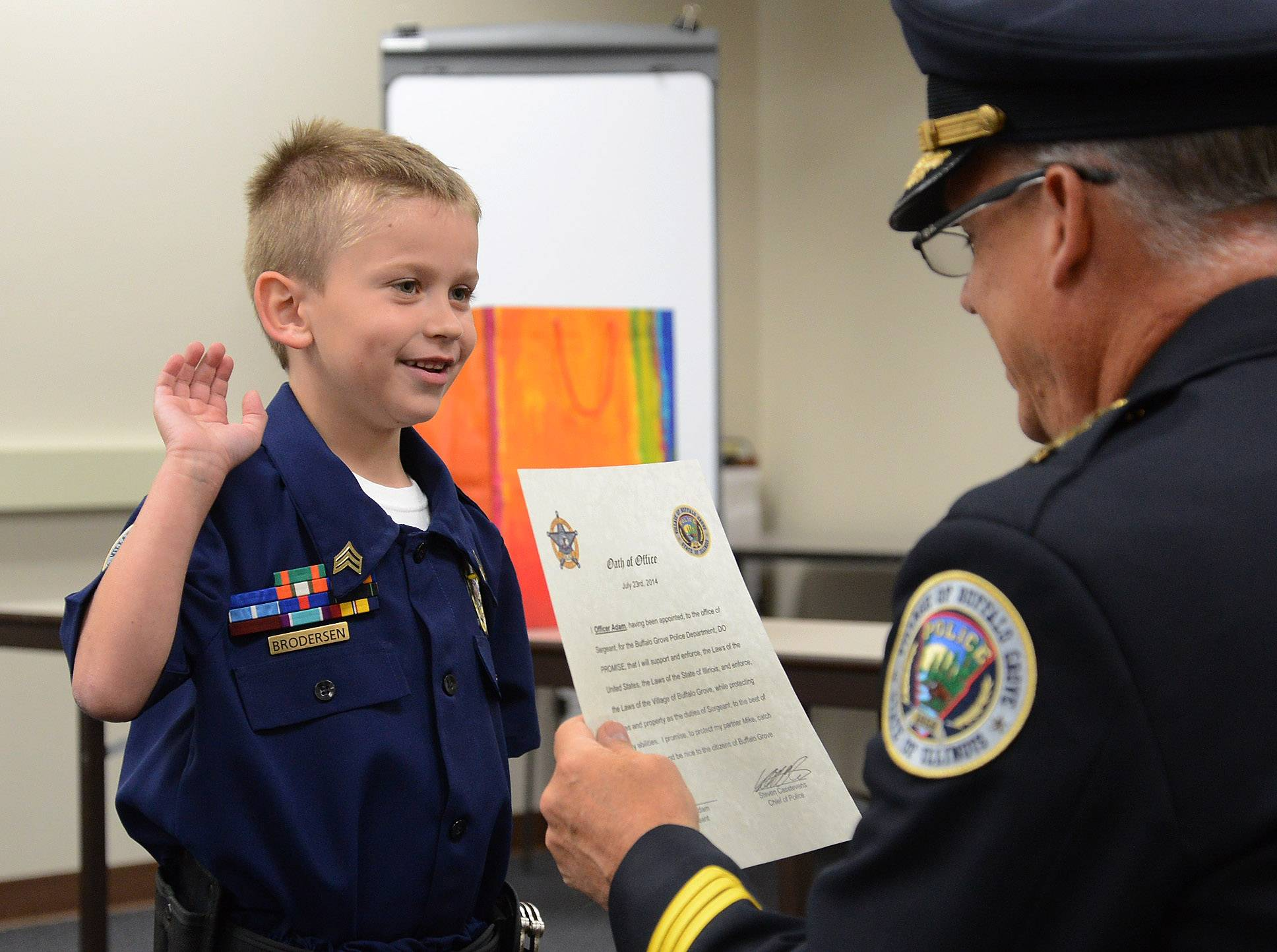 "Seven-year-old Adam Brodersen, of Palatine, being sworn in for ""Cop For A Day"" by Buffalo Grove Chief of Police Steven Casstevens."