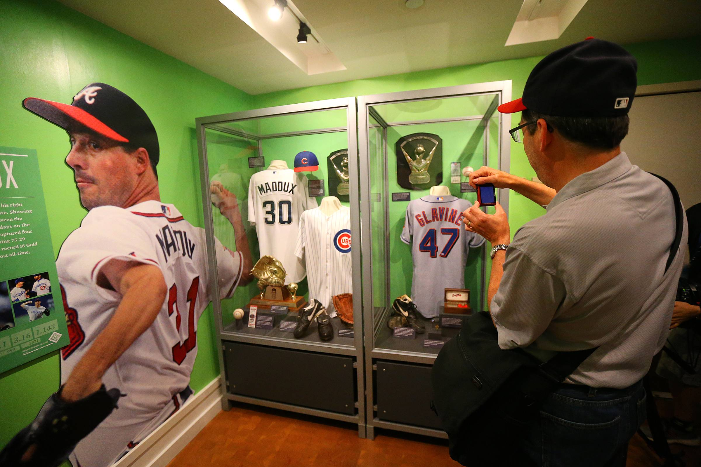 Atlanta Braves fan Mark Fuller snaps a photo of the Tom Glavine and Greg Maddux display at the National Baseball Hall of Fame and Museum on Friday, July 25, 2014, in Cooperstown, N.Y.