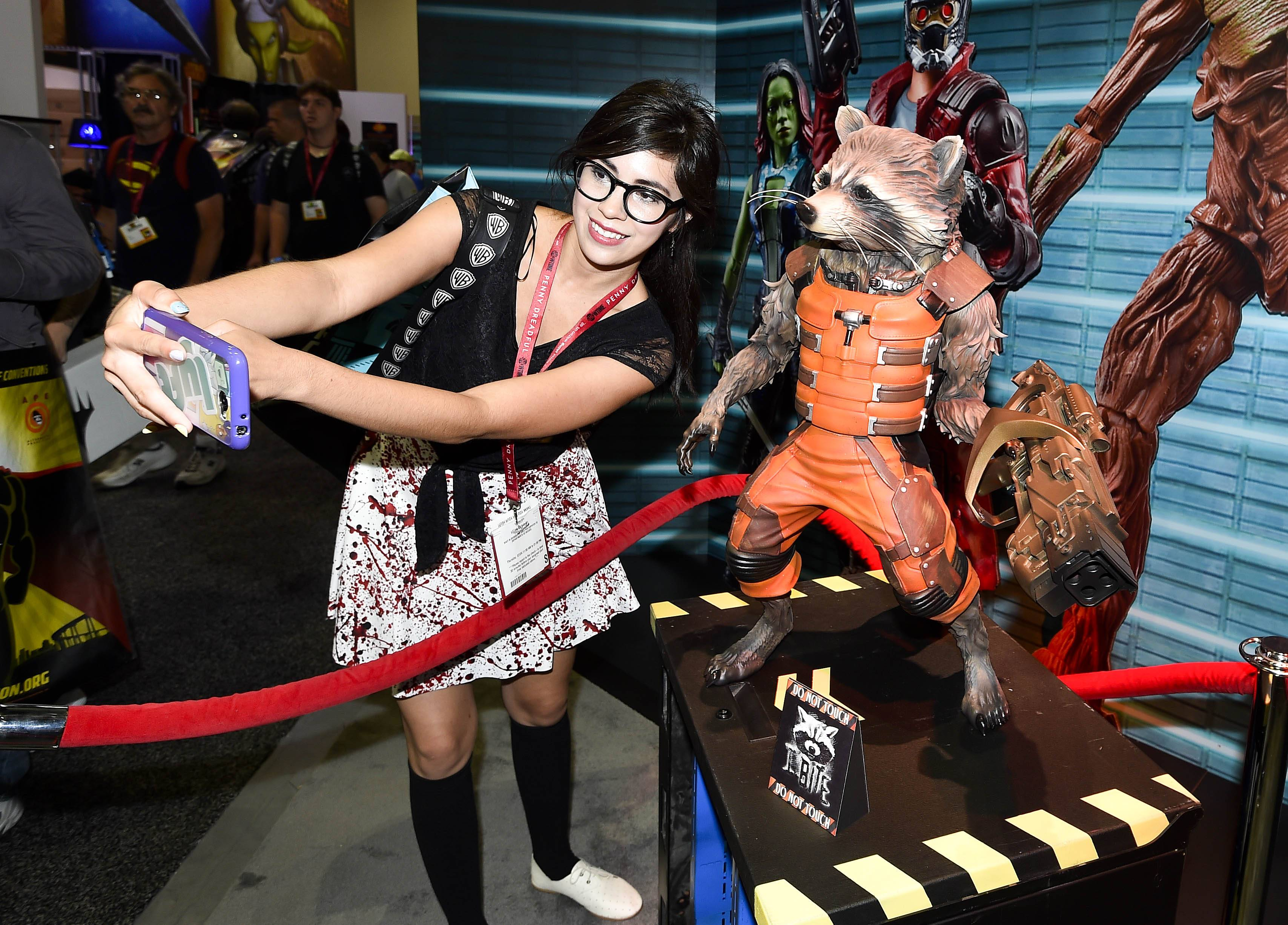 "Monique Soto takes a selife with a ""Guardians of the Galaxy"" Rocket Racoon figurine during preview night Wednesday at the 2014 Comic-Con International Convention."