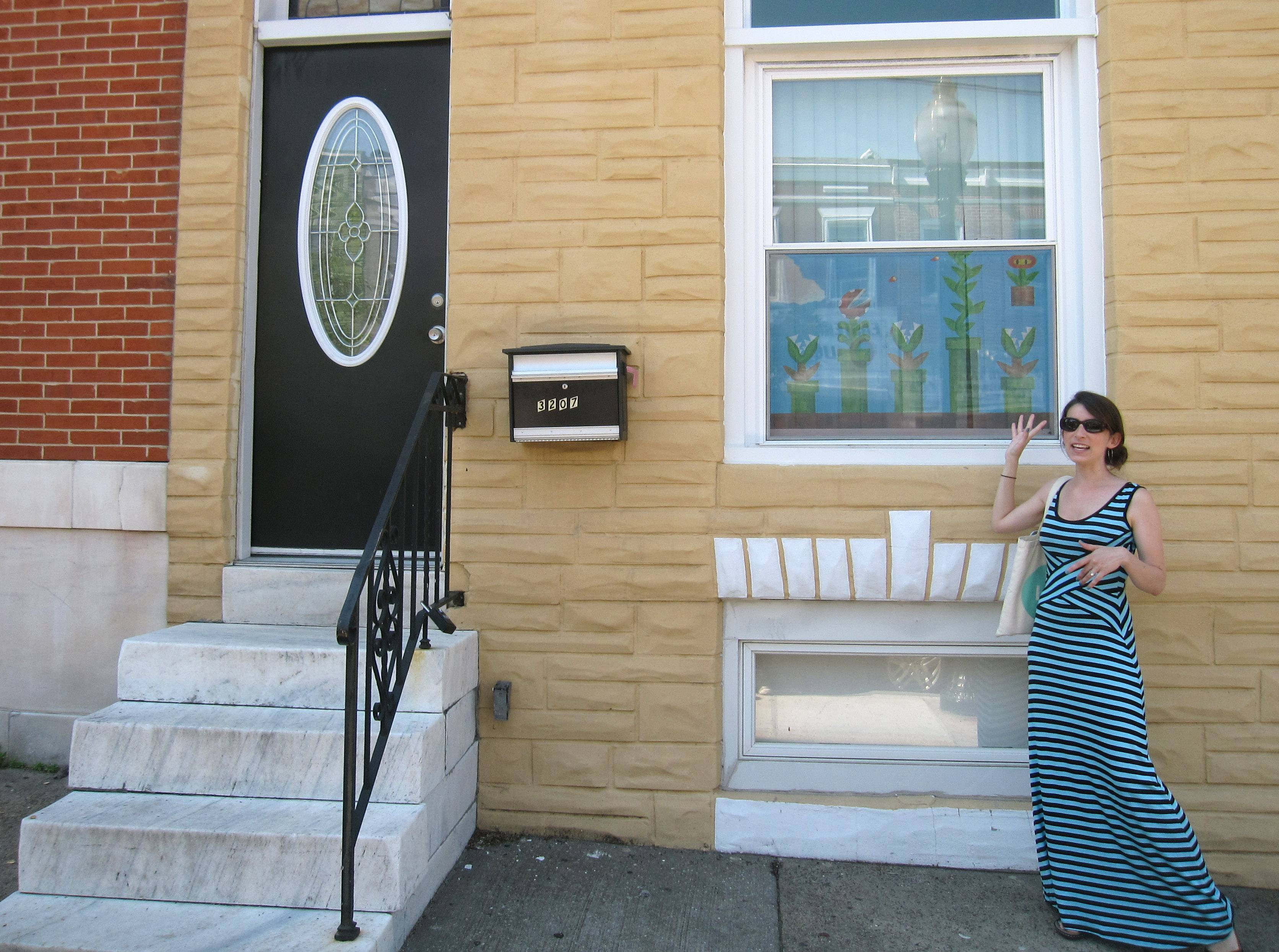 Amanda Smit-Peters shows an example of painted window screens in the Highlandtown neighborhood of Baltimore. Smit-Peters, Main Street manager for the neighborhood, is working with local artists to bring back the urban folk art of painted screens. They were popular in the 20th century as a way to keep people walking by on the street from seeing inside Baltimore's row house windows.