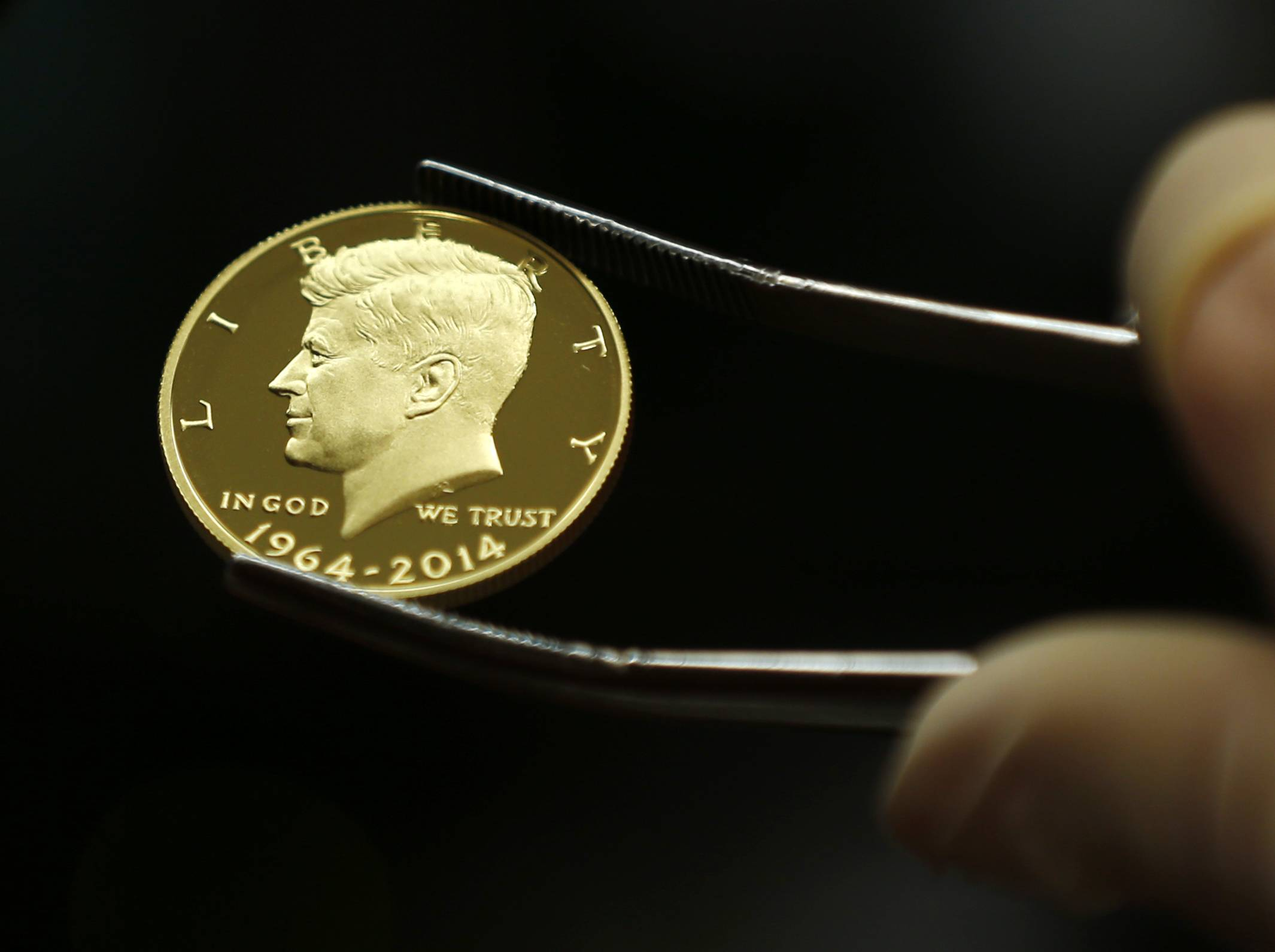A newly-stamped gold coin of President John F. Kennedy is examined at the U.S. Mint at West Point in West Point, N.Y. Kennedy is getting a new look on the new coin that is being made by the mint to mark the 50 years since the slain president debuted on a half-dollar.