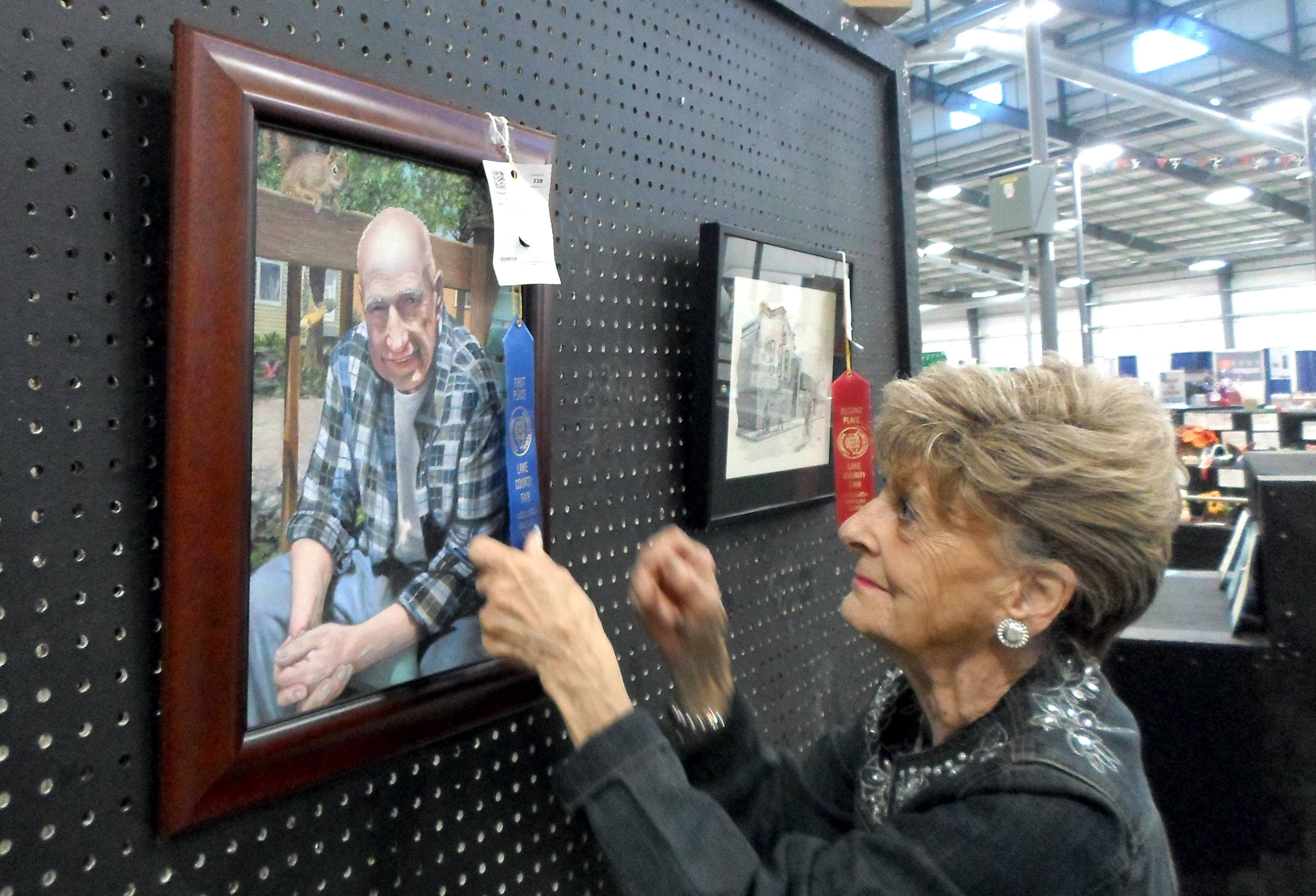 Annie Petersen, in her 62nd year working at the fair, awards the first place and best in show ribbon for paintings on Wednesday. Petersen first fell in love with the fair as a 10-year-old.