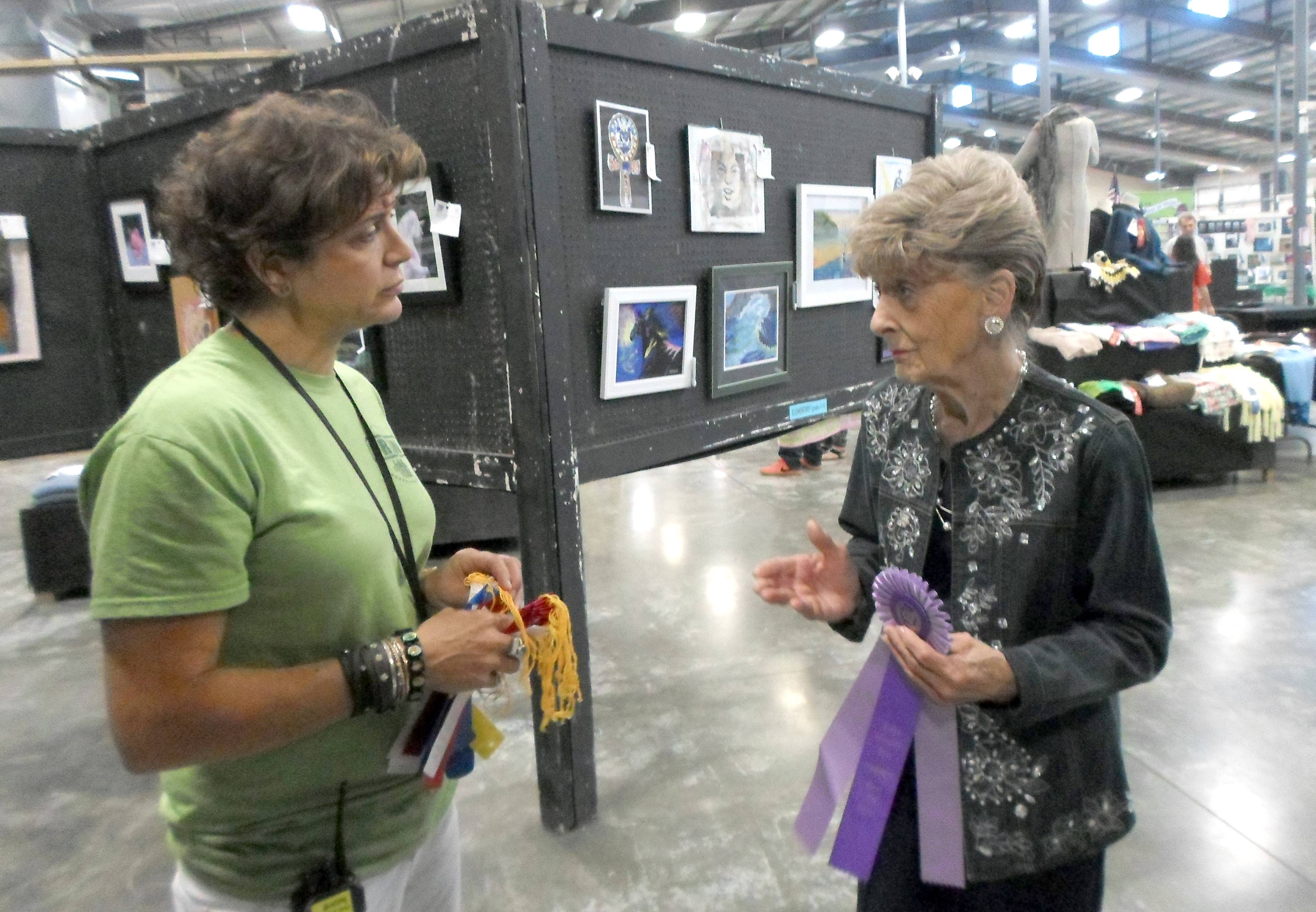 Annie Petersen, who has worked at the Lake County Fair for 62 years, talks Wednesday with Ginny Zerang, fair coordinator for competitions, about how paintings are judged.