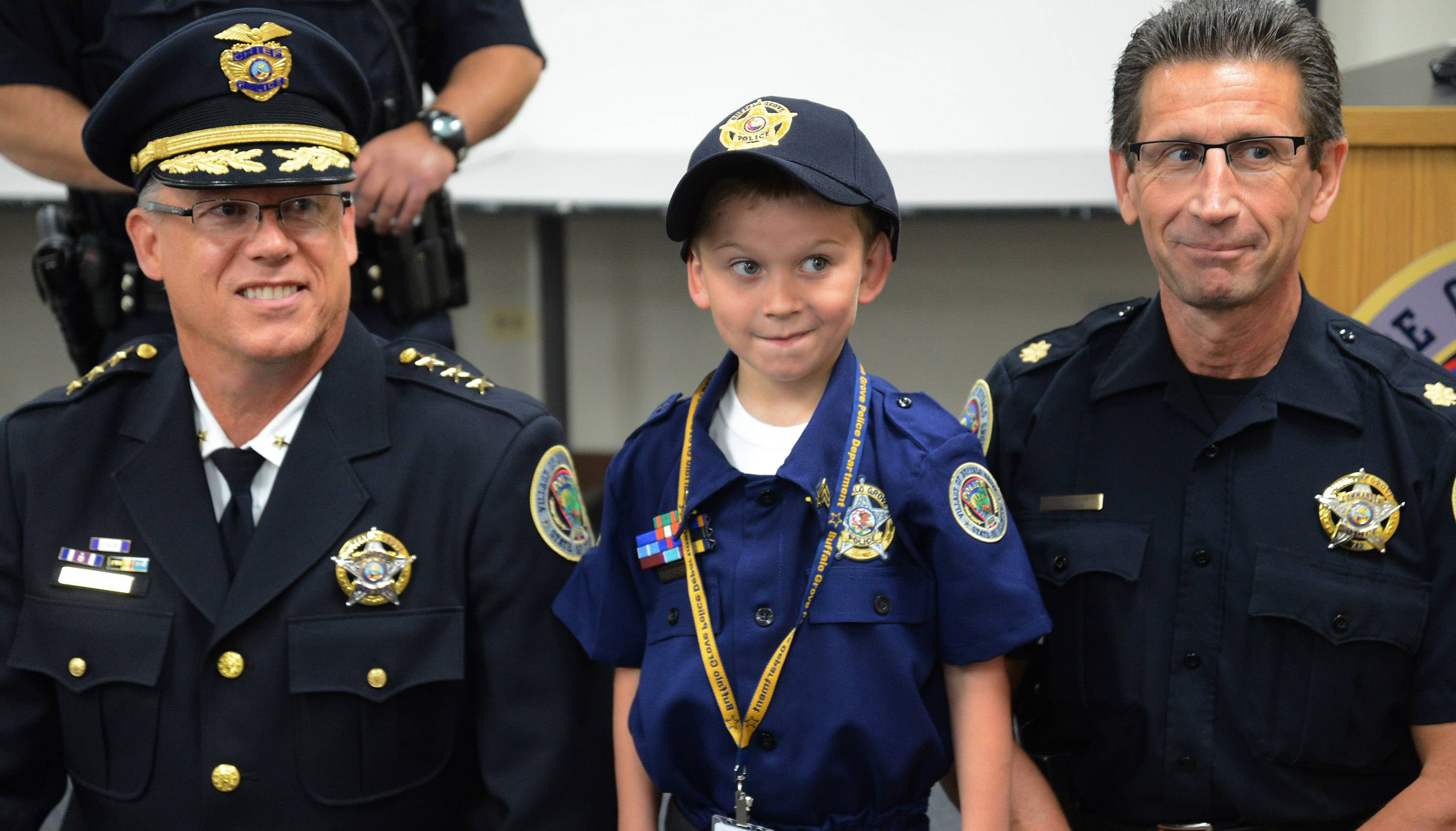 "Adam Brodersen stands with Chief of Police Steven Casstevens, left, and Cmdr. Jim Newton, after being sworn in as ""Cop For A Day"" at the Buffalo Grove police department."