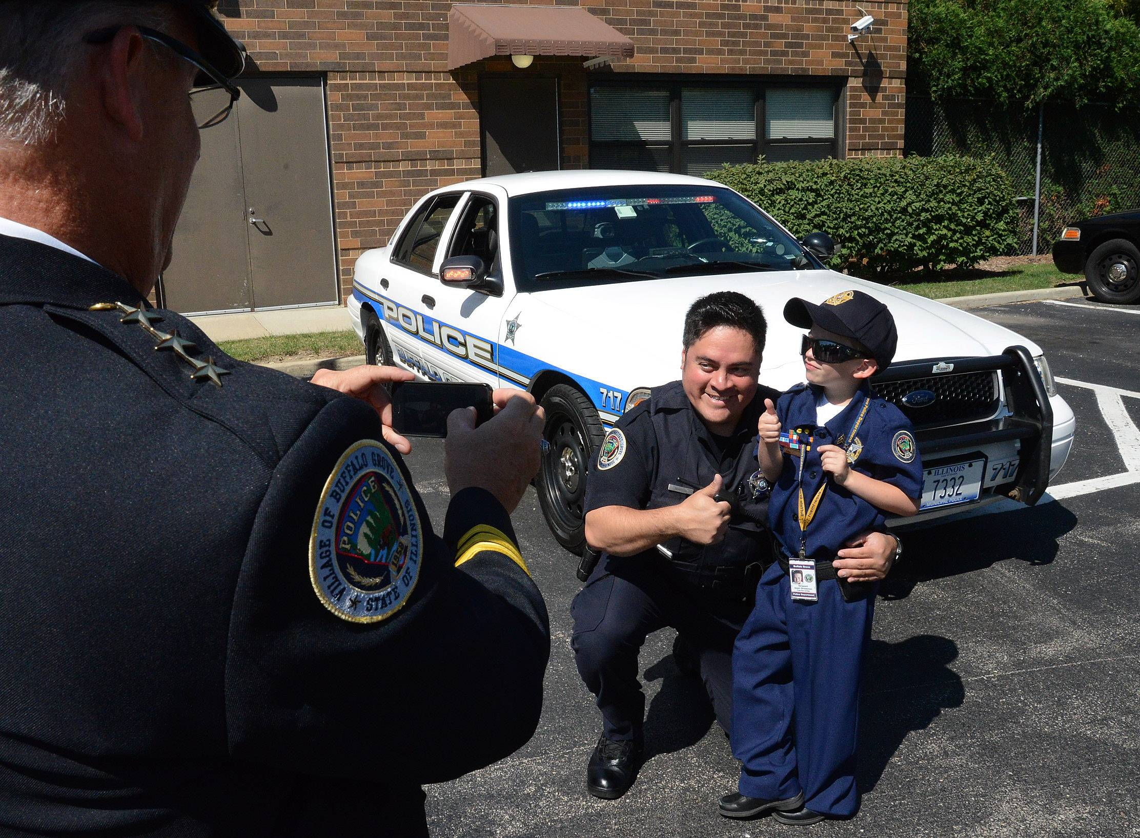 "Seven-year-old Adam Brodersen gets photographed with his partner, Ofc. Mike Martin, by Chief of Police Steven Casstevens during ""Cop For A Day"" at the Buffalo Grove police department."