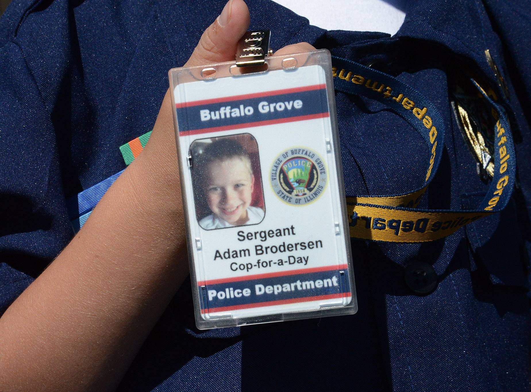 "Adam Brodersen holds his official ID badge as ""Cop For A Day"" at the Buffalo Grove police department."